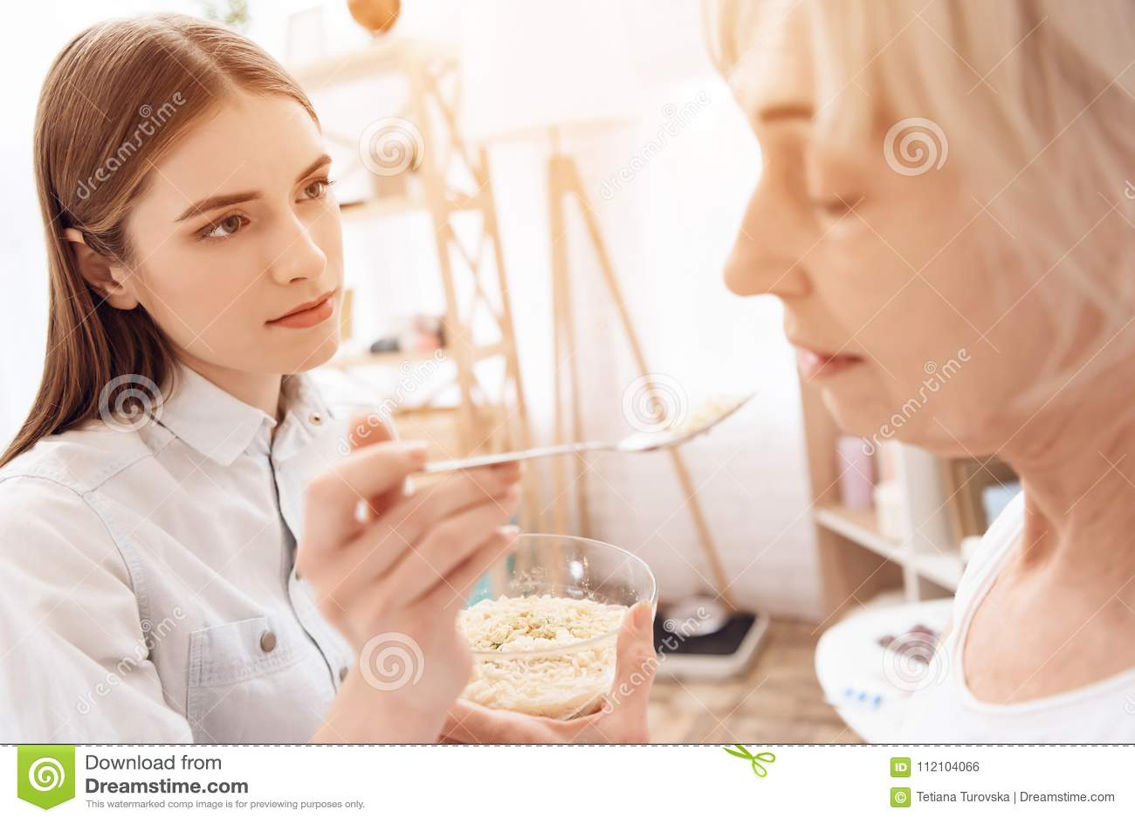 A menina está nutrindo a mulher idosa em casa A menina está ajudando a mulher com alimento