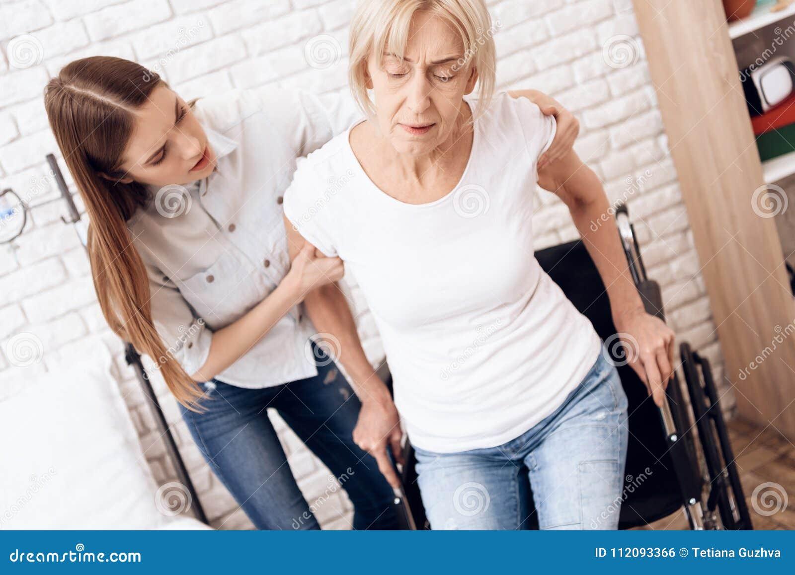 A menina está nutrindo a mulher idosa em casa A menina está ajudando a mulher a obter na cadeira de rodas