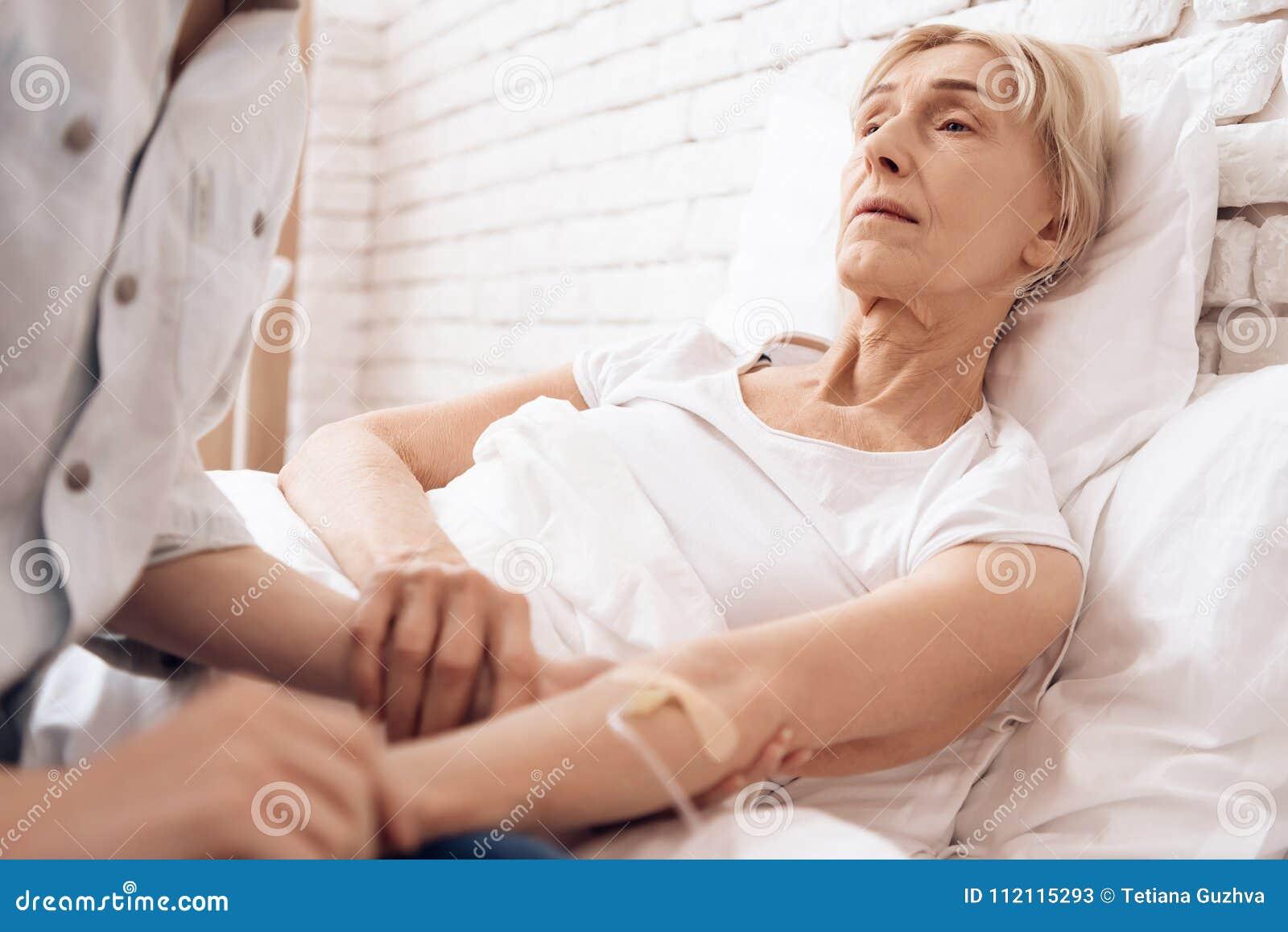 A menina está nutrindo a mulher idosa em casa Estão guardando as mãos A mulher é conectada ao contador da gota