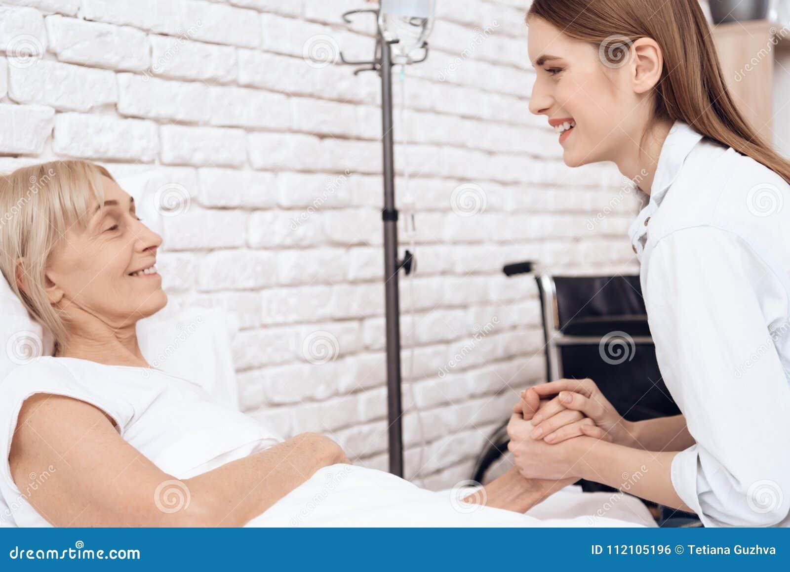 A menina está nutrindo a mulher idosa em casa Estão guardando as mãos, rindo