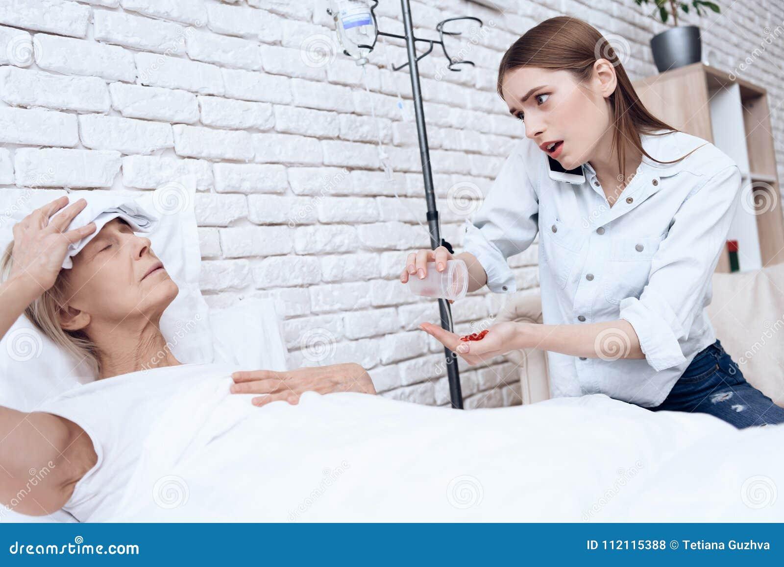 A menina está nutrindo a mulher idosa em casa A menina está no telefone, dando comprimidos à mulher