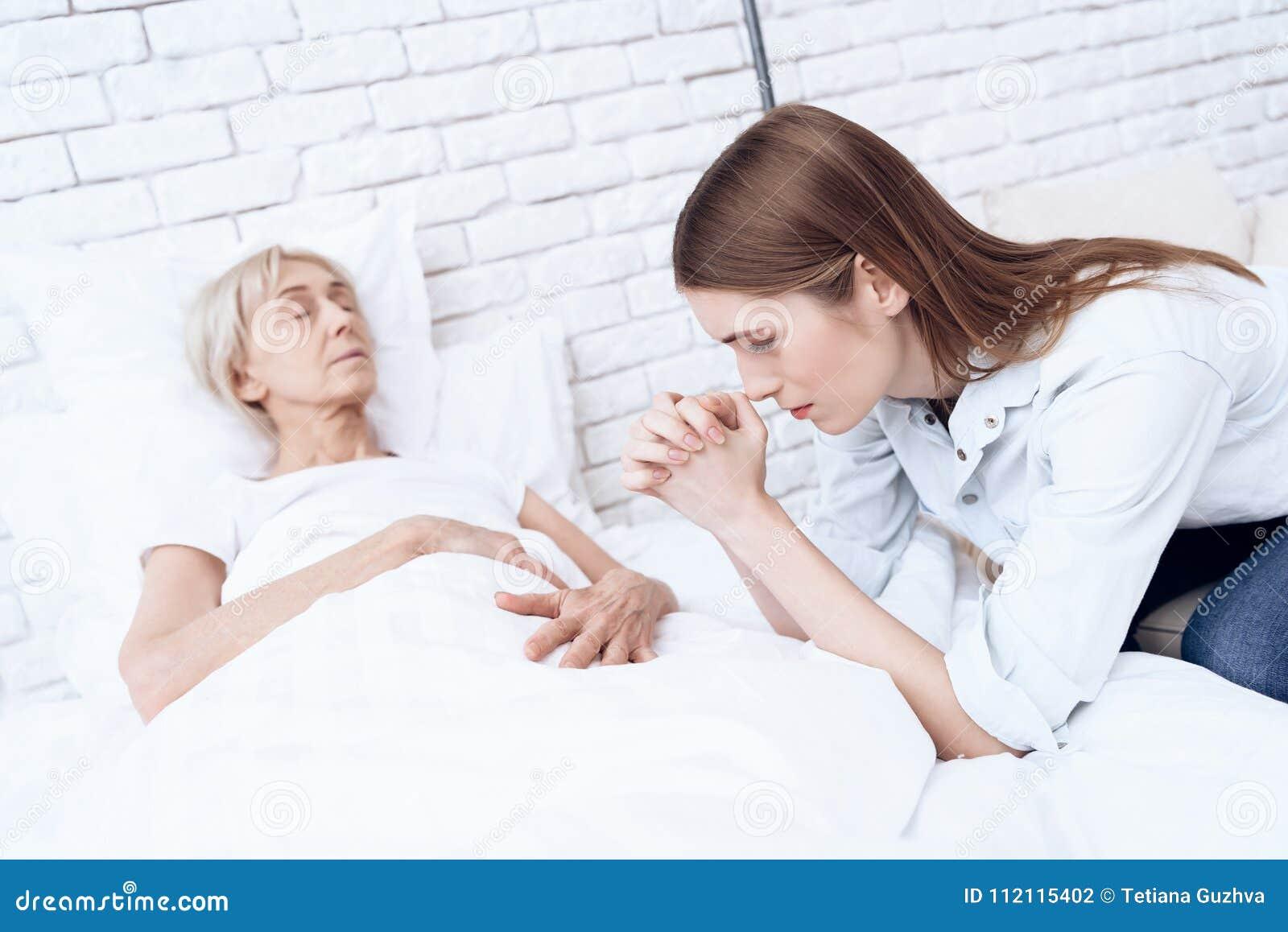 A menina está nutrindo a mulher idosa em casa A mulher está sentindo má, menina está rezando