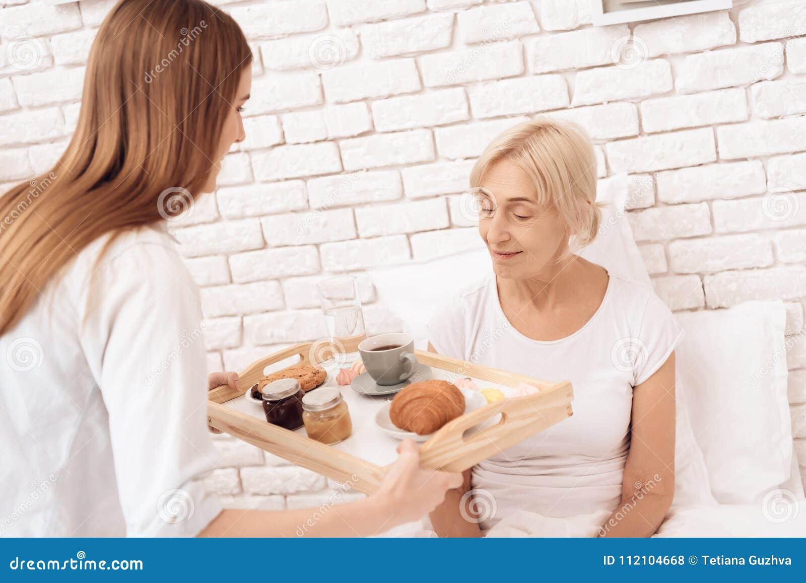 A menina está nutrindo a mulher idosa em casa A menina traz o café da manhã na bandeja