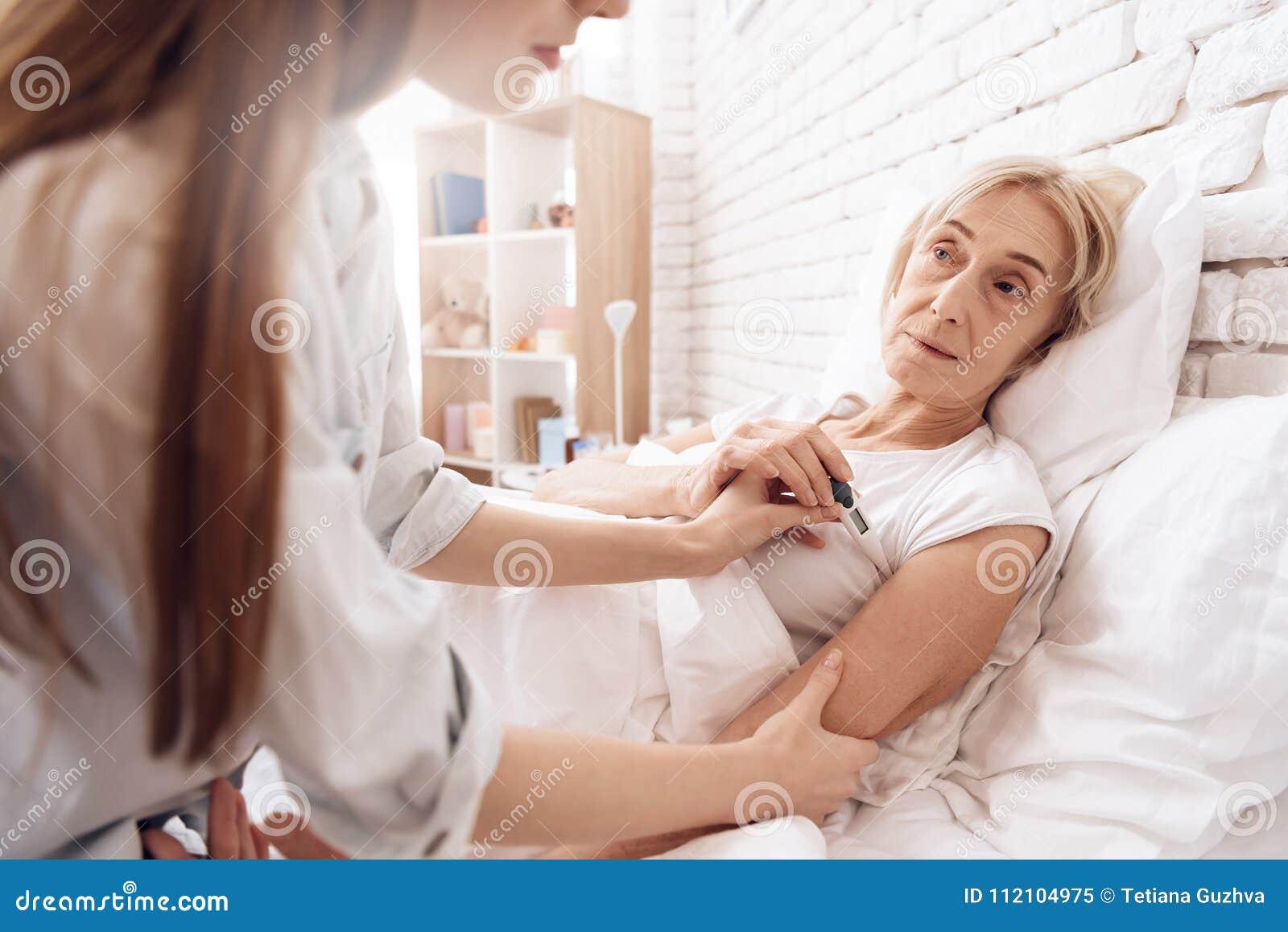 A menina está nutrindo a mulher idosa em casa A menina está verificando a temperatura com o termômetro eletrônico