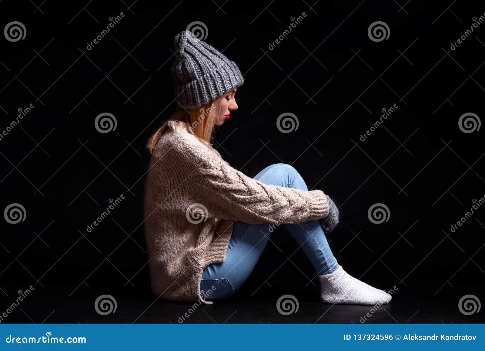 A menina está sentando-se apenas no assoalho em um fundo preto do vazio, abraçando seus pés com suas mãos e olhando para baixo,