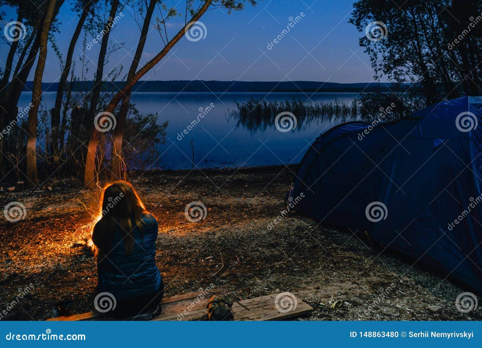 A menina est? sentando-se perto da fogueira A barraca de acampamento azul iluminou para dentro Acampamento das horas da noite Rec