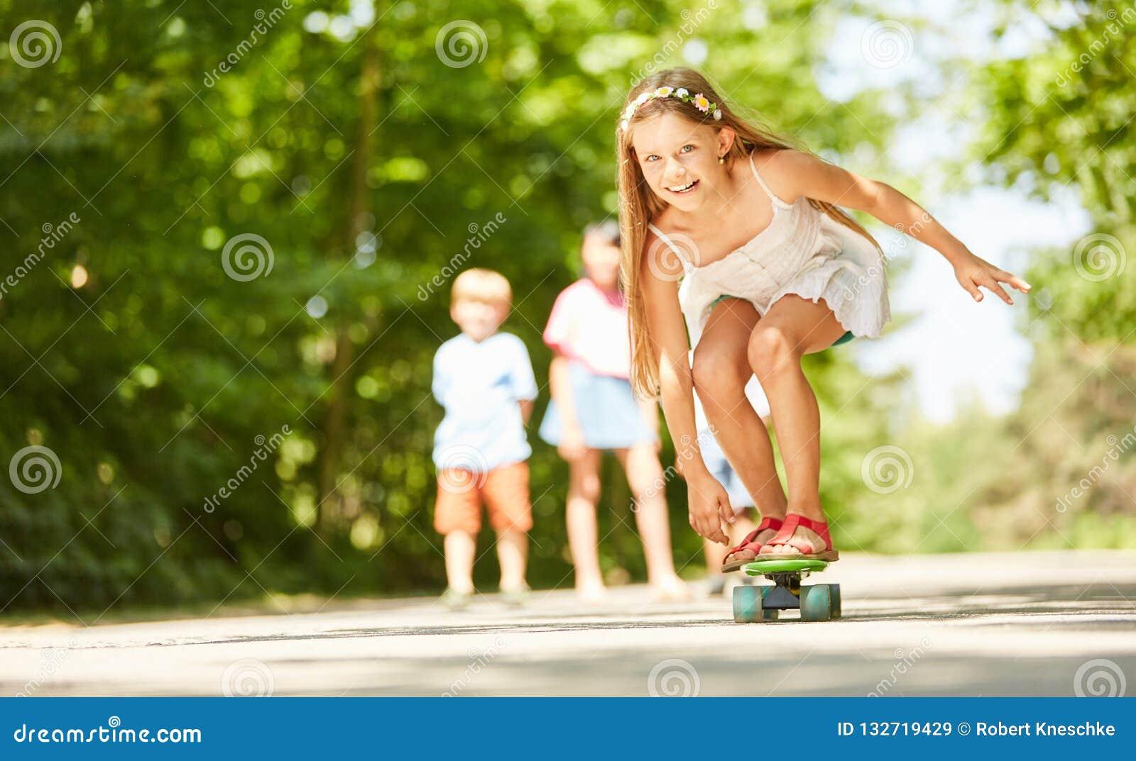 A menina está tendo o divertimento ao skateboarding