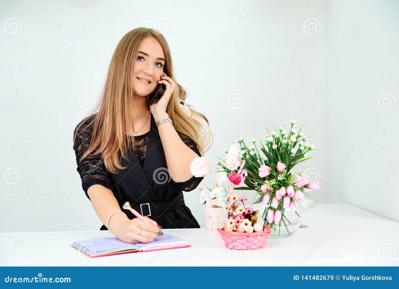 A menina europeia bonita toma para chamar o telefone e escreve em um caderno em um fundo branco Estão próximo as flores e