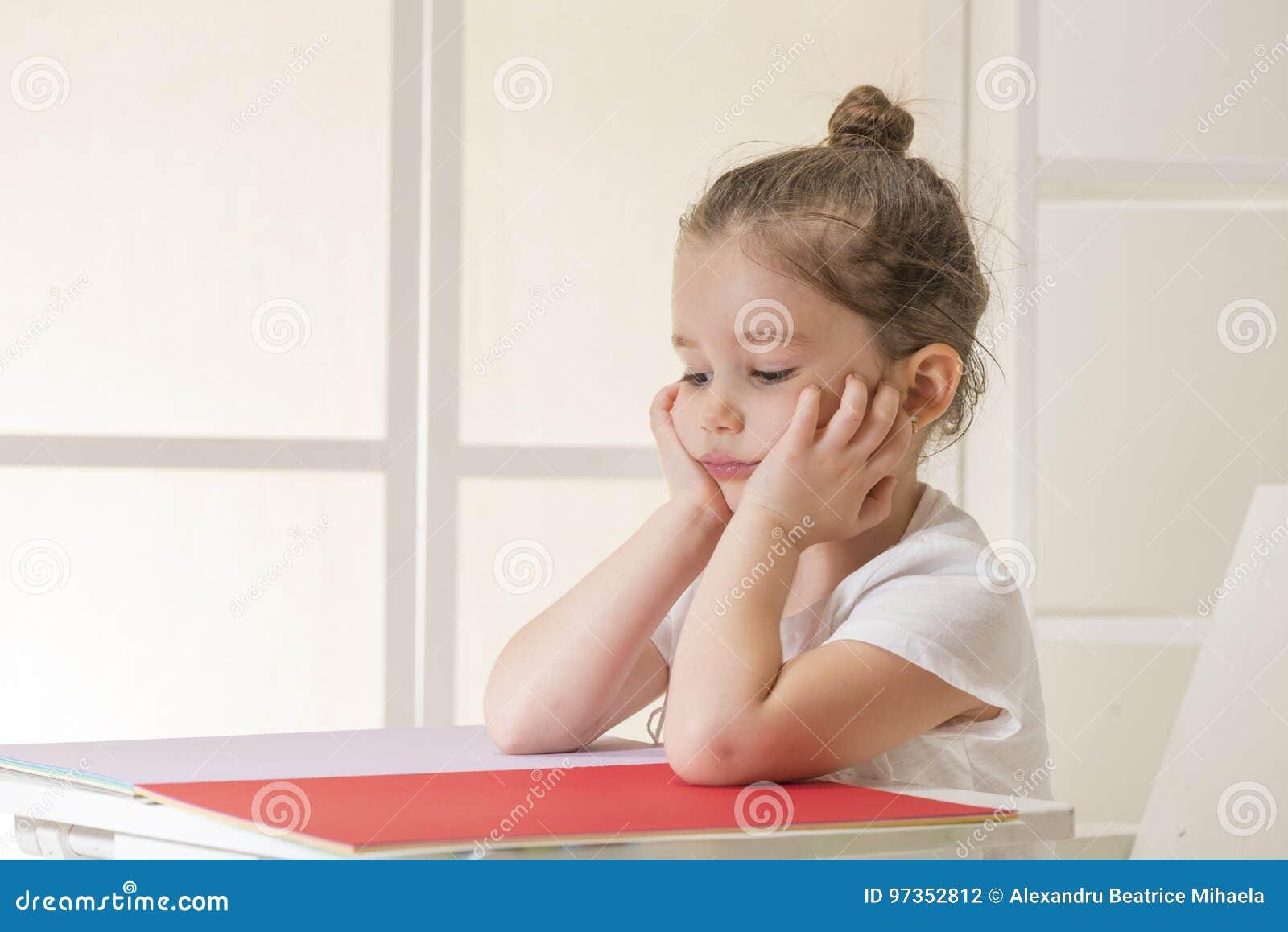 Menina expressivo que senta-se na espera da mesa