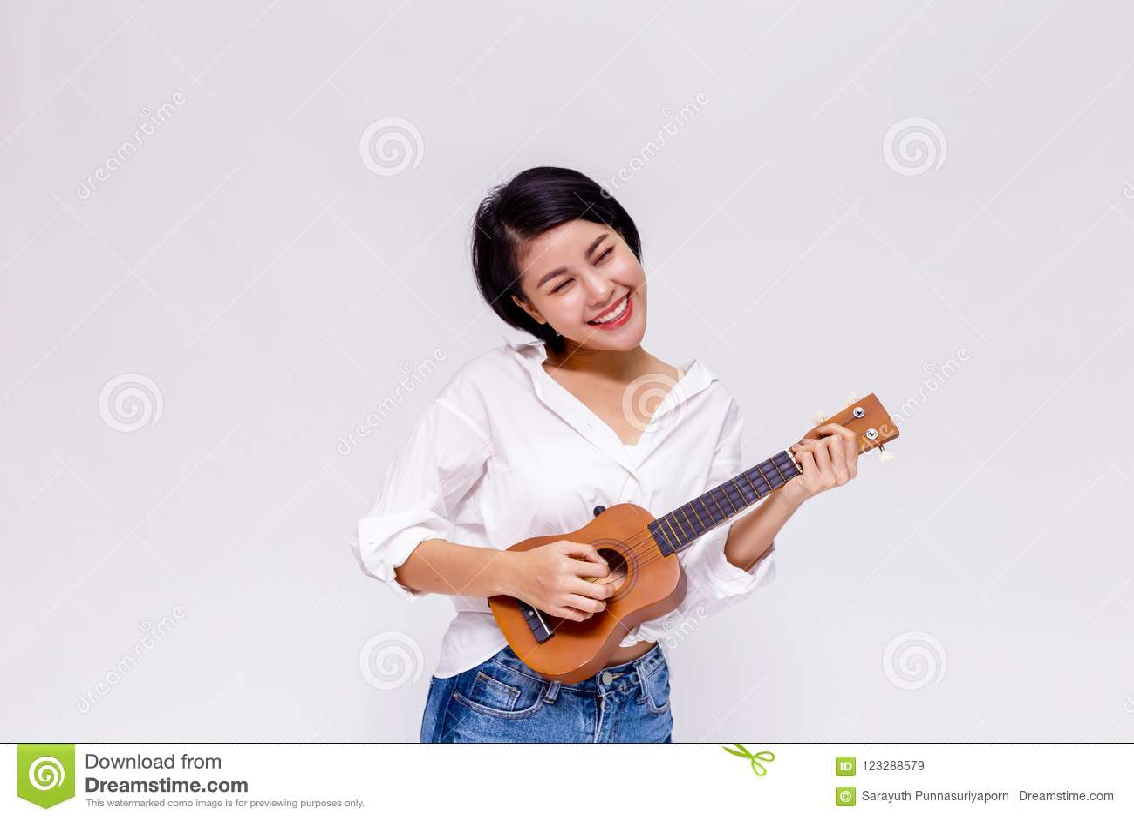 Menina fêmea asiática nova que joga a guitarra da praia da uquelele no fundo isolado branco