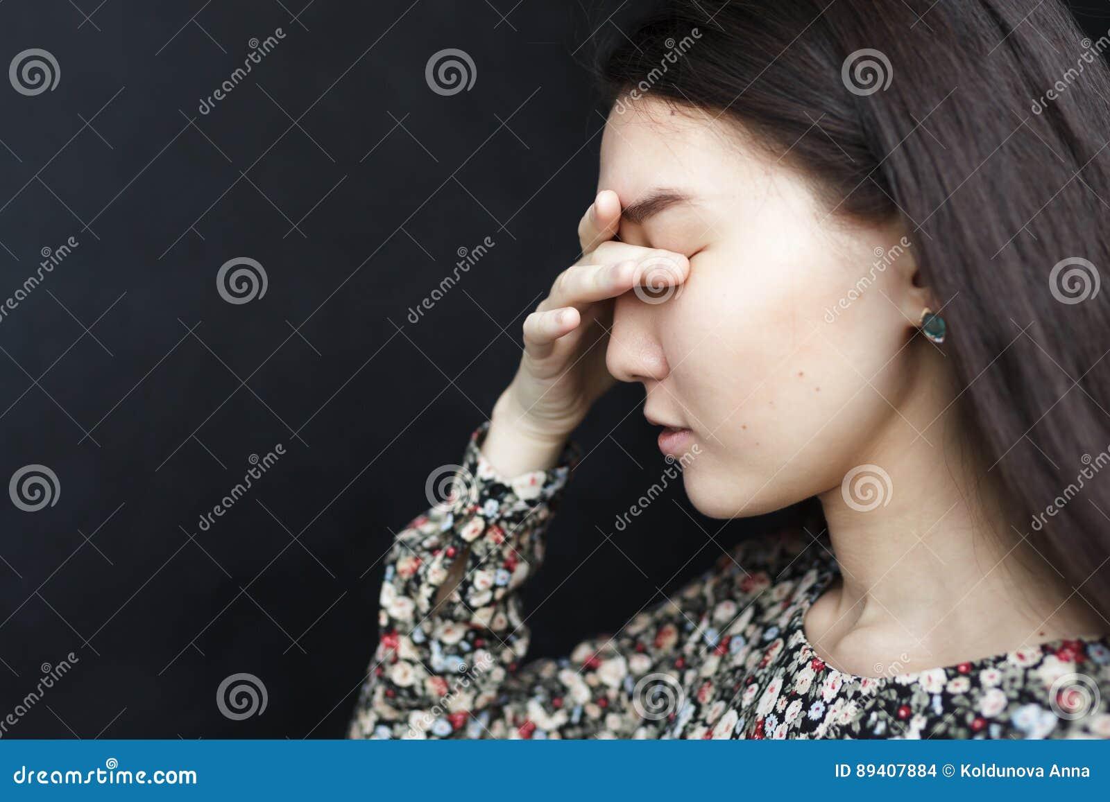 A menina fecha seus olhos com sua palma A dor de cabeça ou a enxaqueca, sofrem da depressão e da solidão