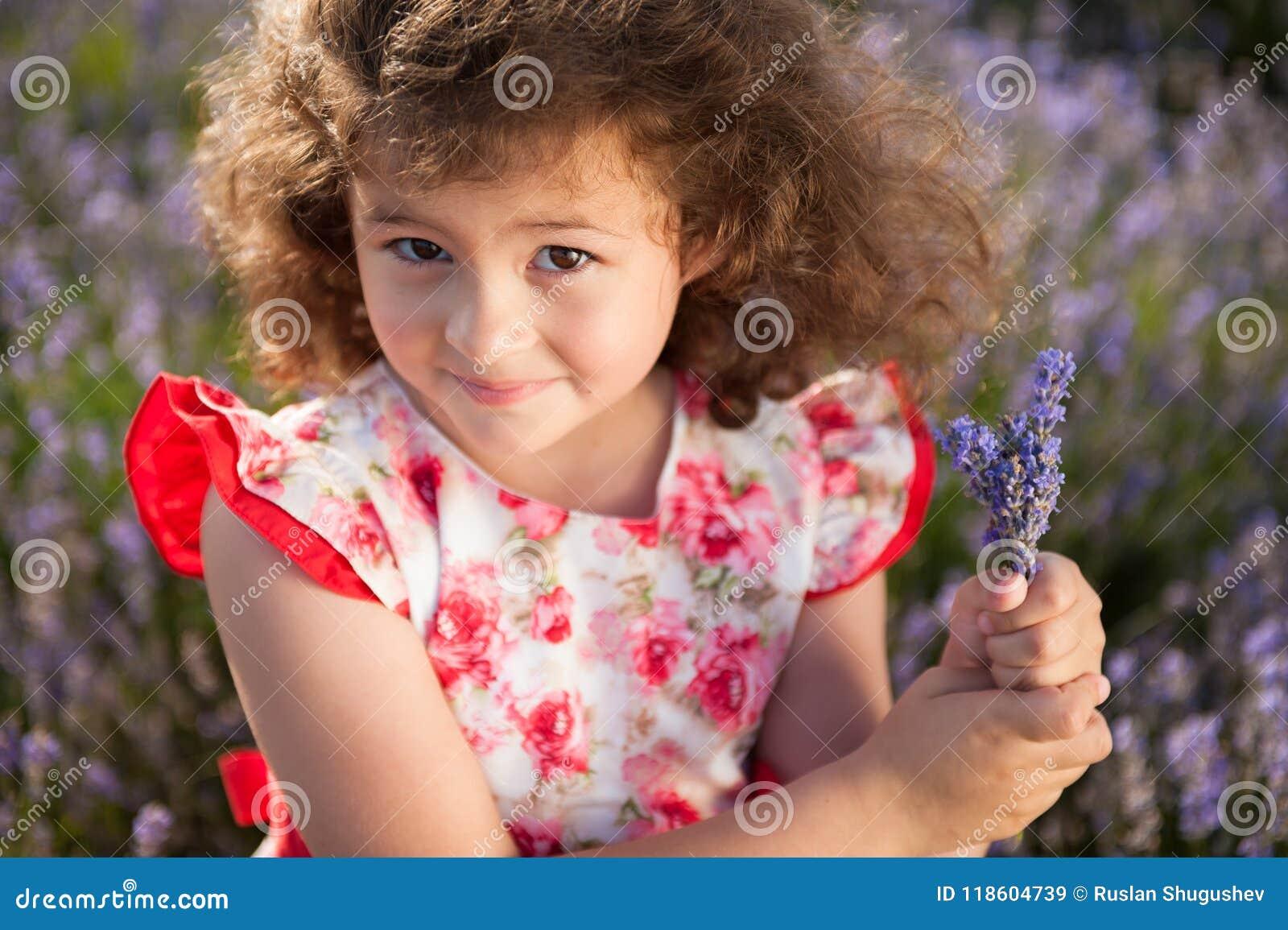 Menina feliz bonita com o ramalhete de flores do verão no campo da alfazema