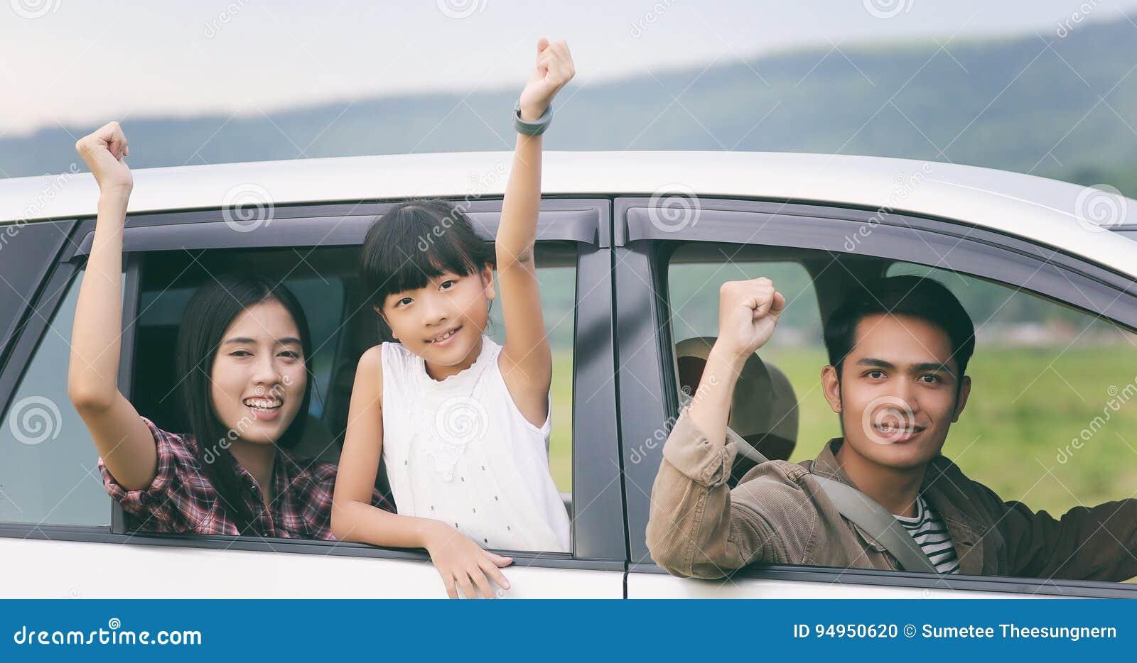 Menina feliz com a família asiática que senta-se no carro para o enjo
