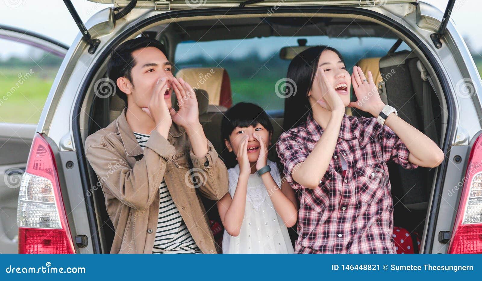 Menina feliz com a fam?lia asi?tica que senta-se no carro para apreciar f?rias da viagem por estrada e de ver?o na camionete de c
