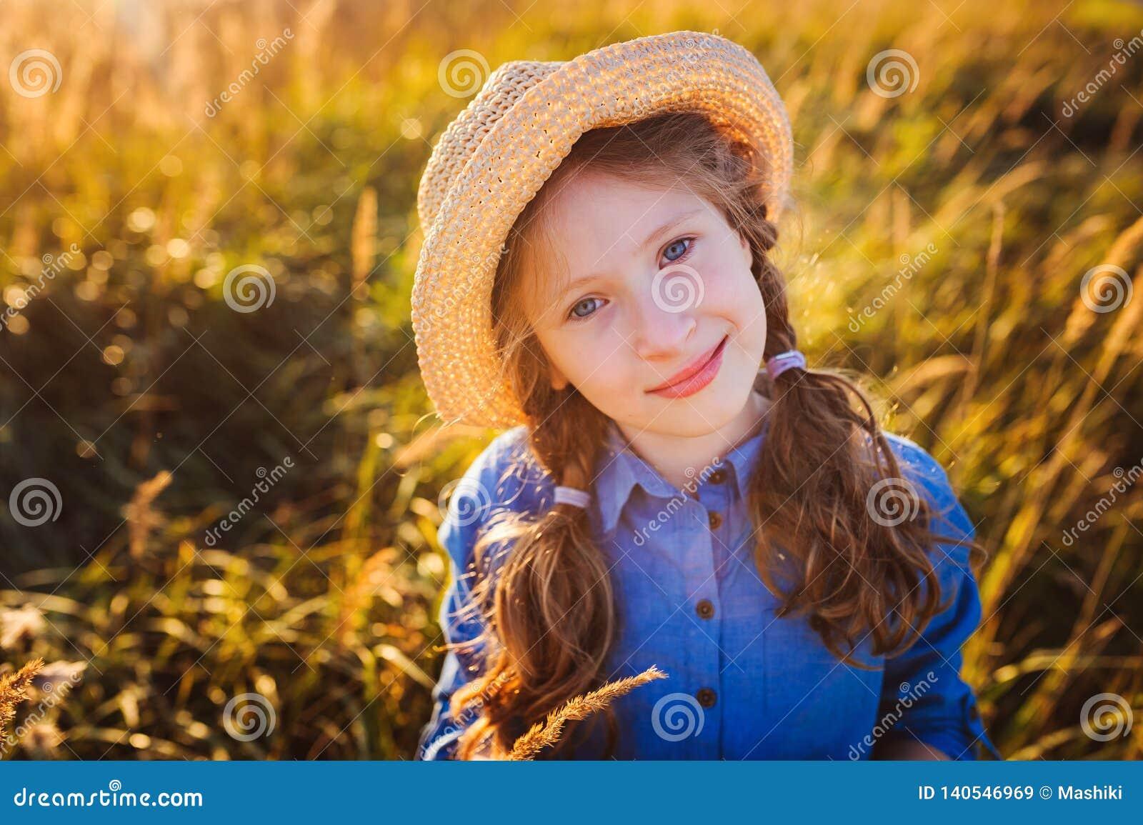 Menina feliz da criança no vestido e na palha azuis que anda no prado ensolarado do verão