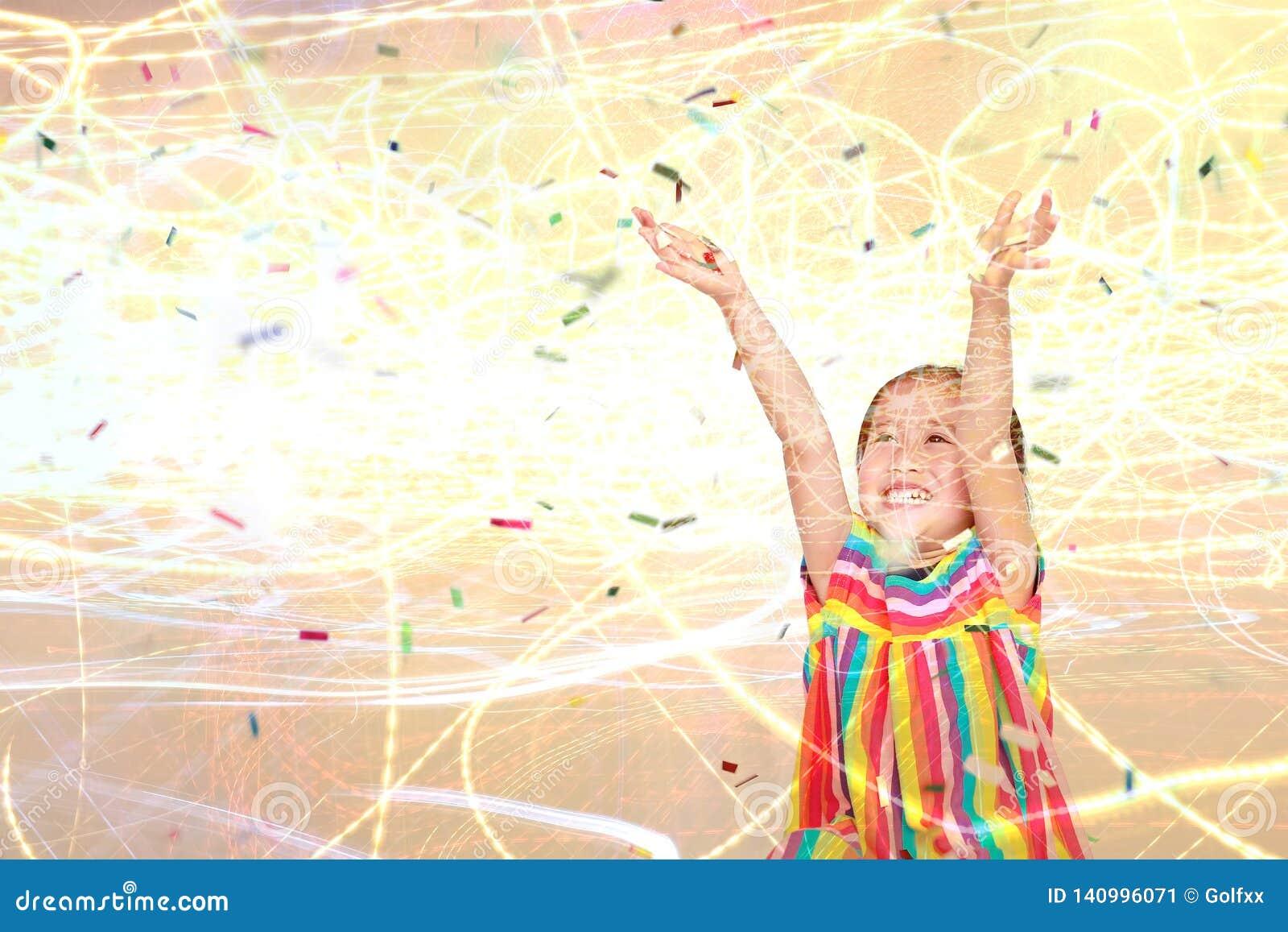 Menina feliz da criança pequena de exposição dobro com confetes coloridos e fundo claro Ano novo feliz ou conceito das felicitaçõ