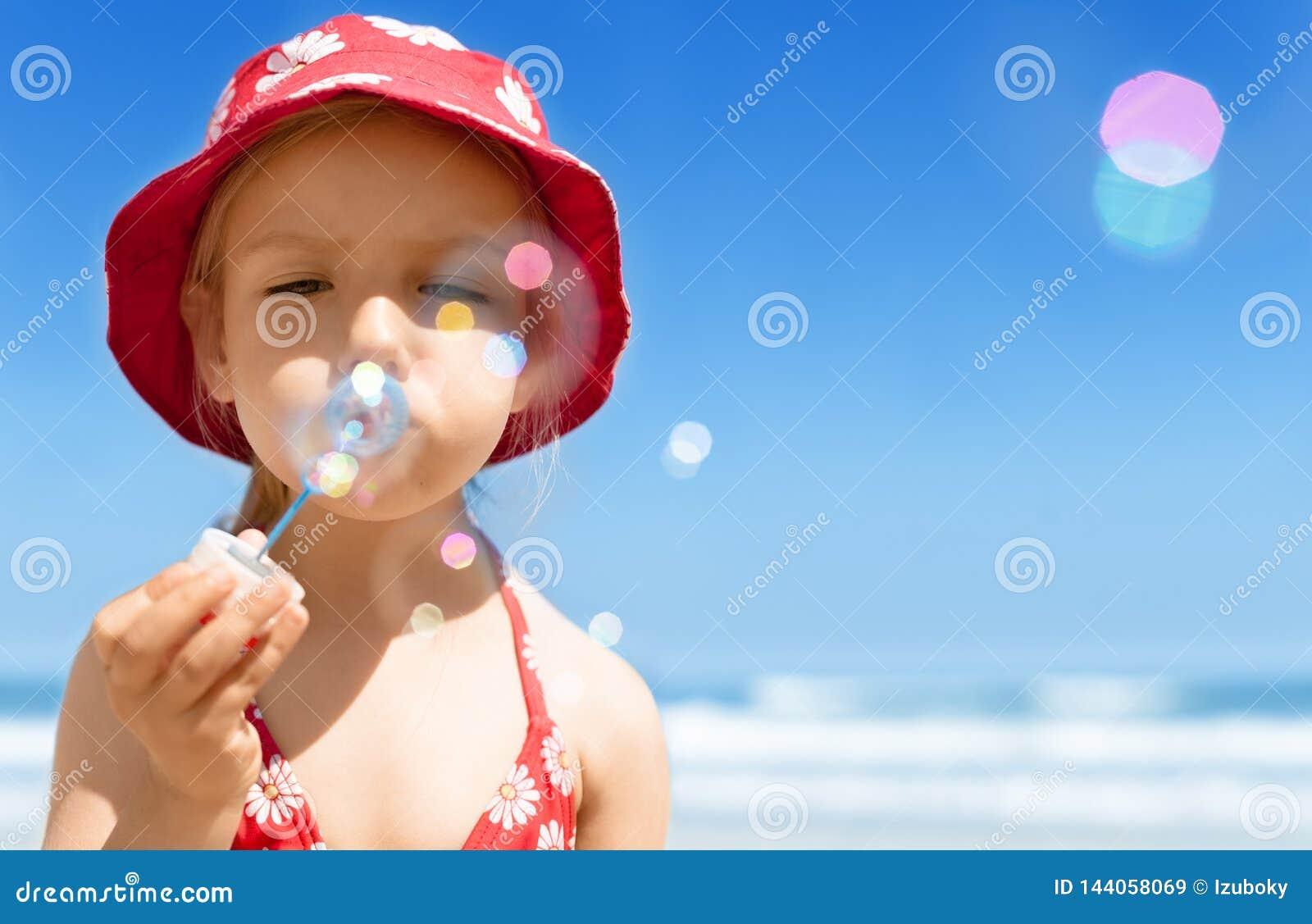 Menina feliz de sopro da criança das bolhas de sabão, jogando, tendo o divertimento na praia do verão