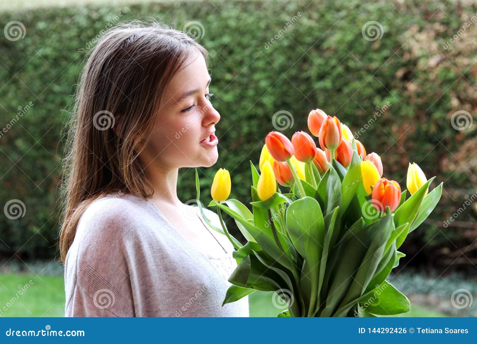 Menina feliz de sorriso bonita do tween que guarda o ramalhete grande das tulipas amarelas e alaranjadas brilhantes que falam a e