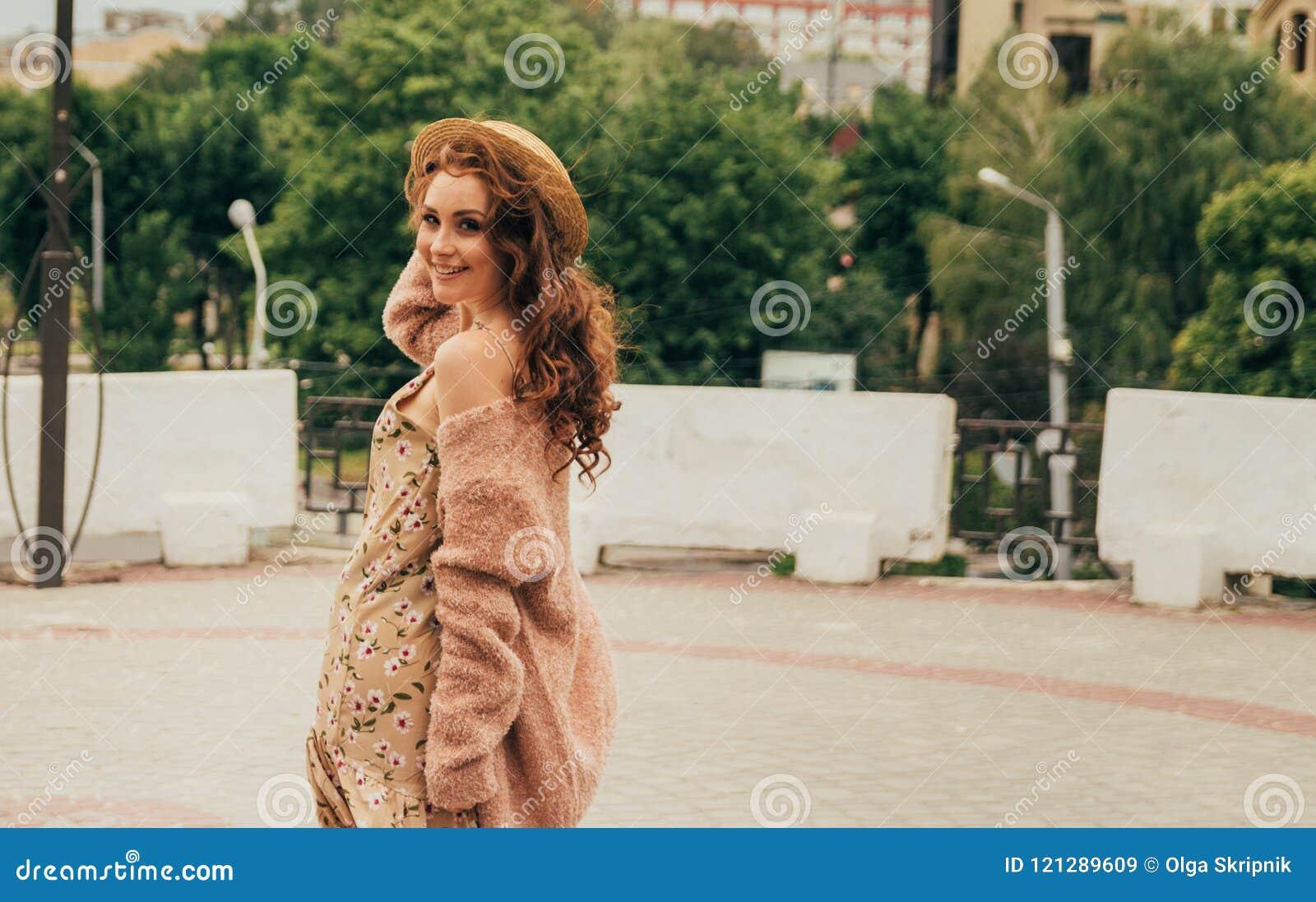 Menina feliz de sorriso no vestido e no chapéu em uma rua da cidade e em olhar a câmera em um chapéu, em um vestido em uma flor e