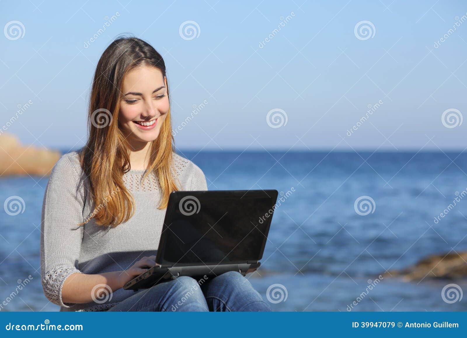 Menina feliz do adolescente que consulta meios sociais na praia