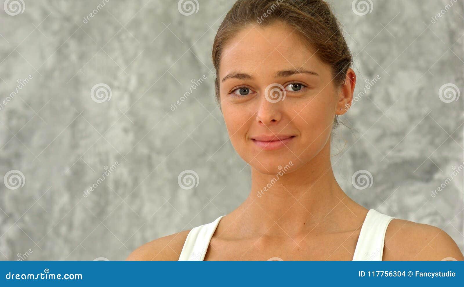 Menina feliz do ajuste que sorri e que olha a câmera