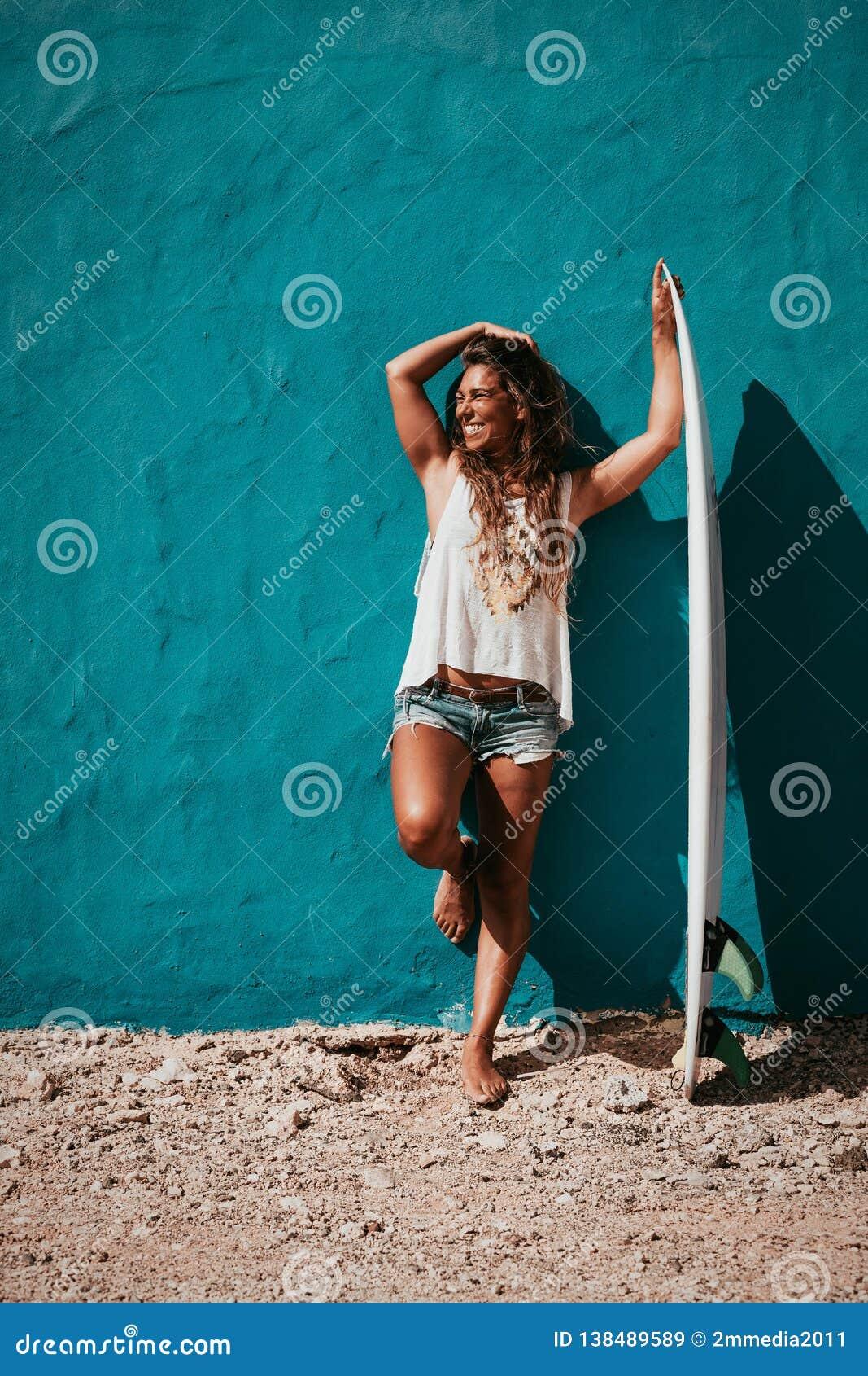 Menina feliz do surfista com a prancha na frente da parede azul