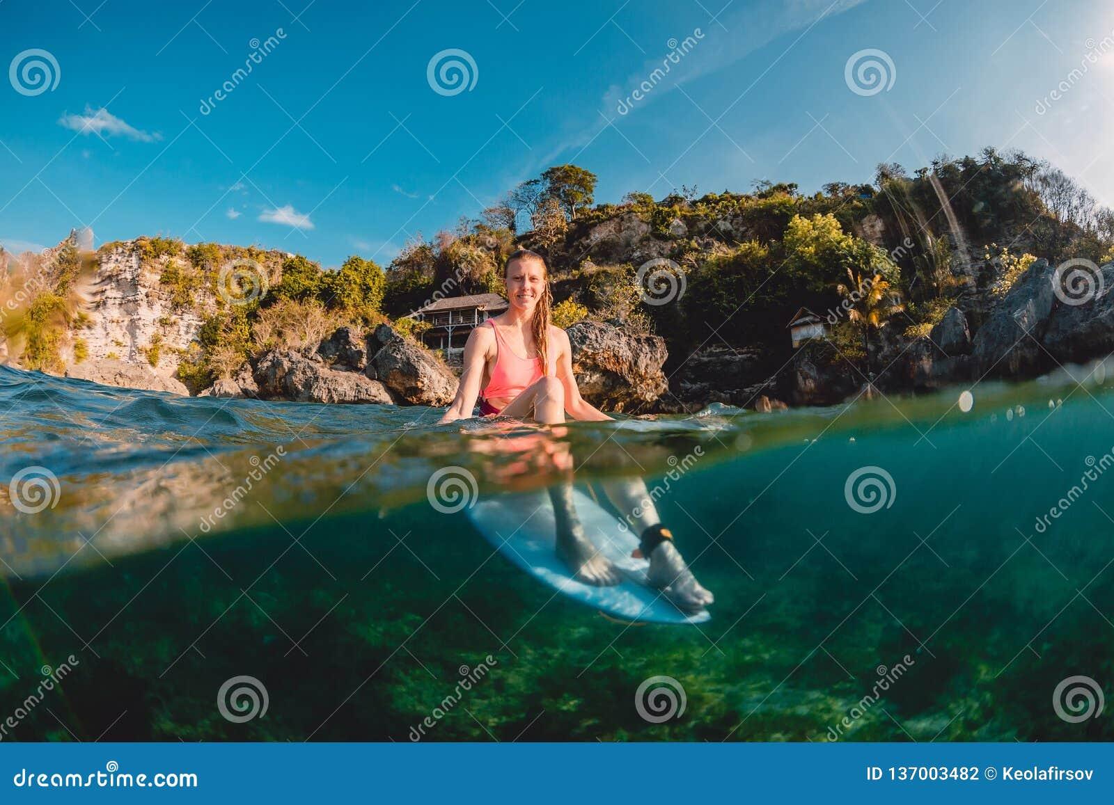 Menina feliz do surfista com prancha O surfista senta-se na placa no oceano