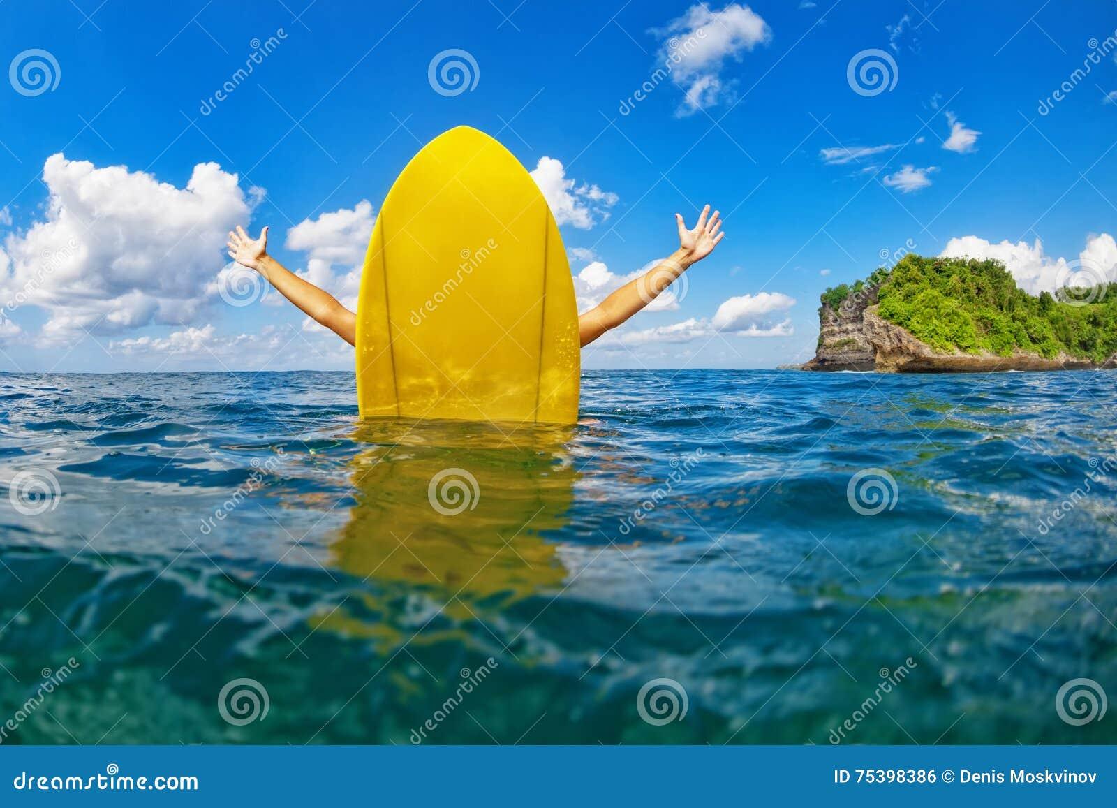 A menina feliz do surfista senta-se na prancha amarela no oceano