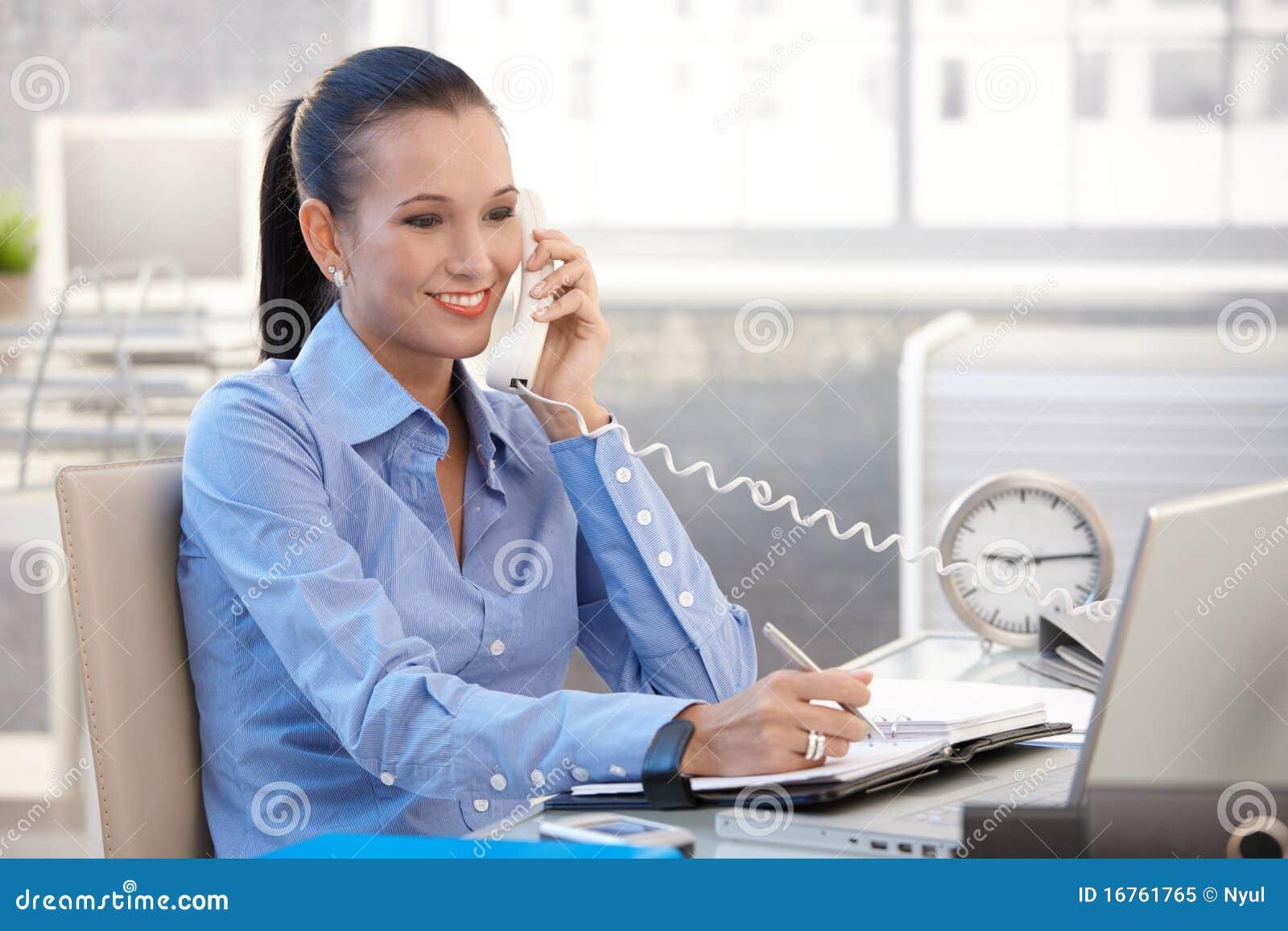 Menina feliz do trabalhador de escritório no atendimento de telefone