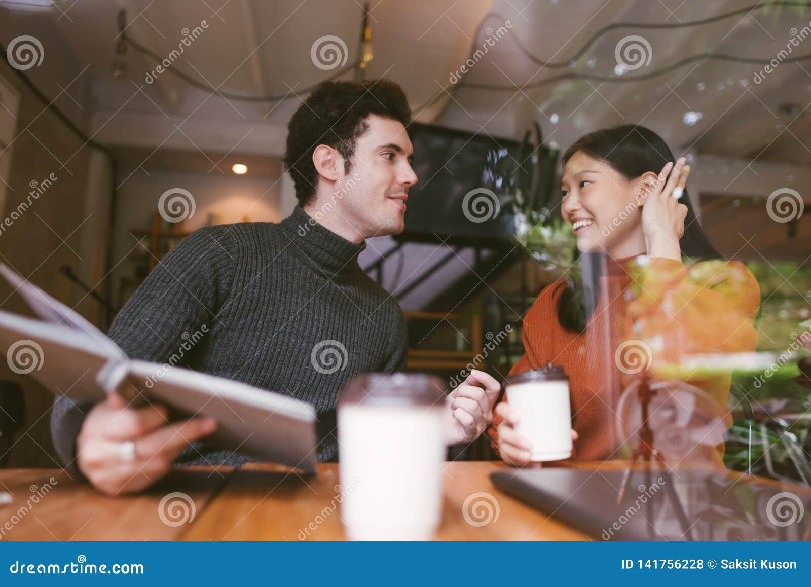 Menina feliz e amigos asiáticos que conversam a fala no café da cafetaria na universidade para manter o contato de olho e o riso