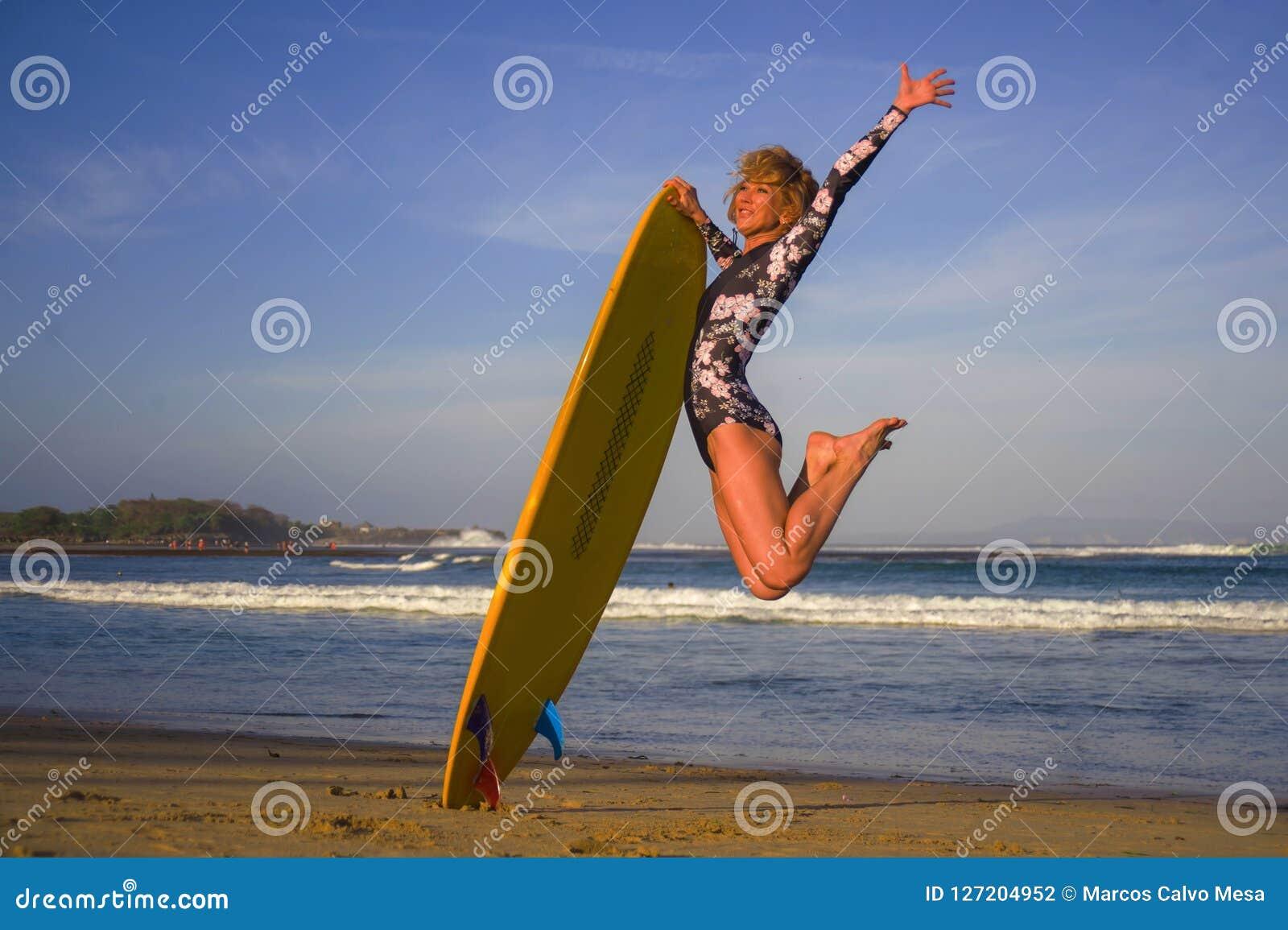 A menina feliz e atrativa nova do surfista que salta altamente no ar que guarda a placa de ressaca antes de surfar na praia tropi