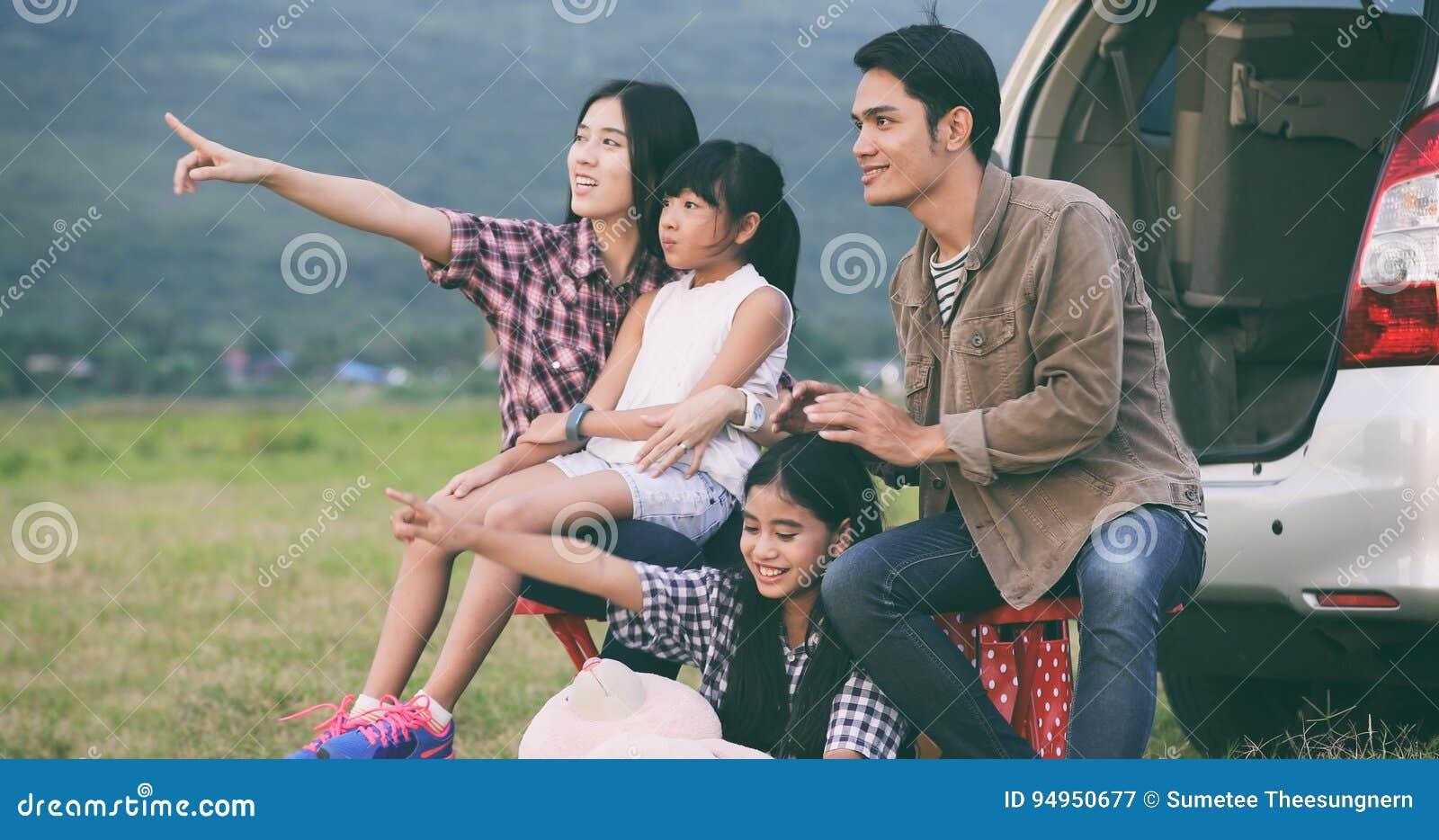 Menina feliz e com a família asiática que senta-se no carro para o enj