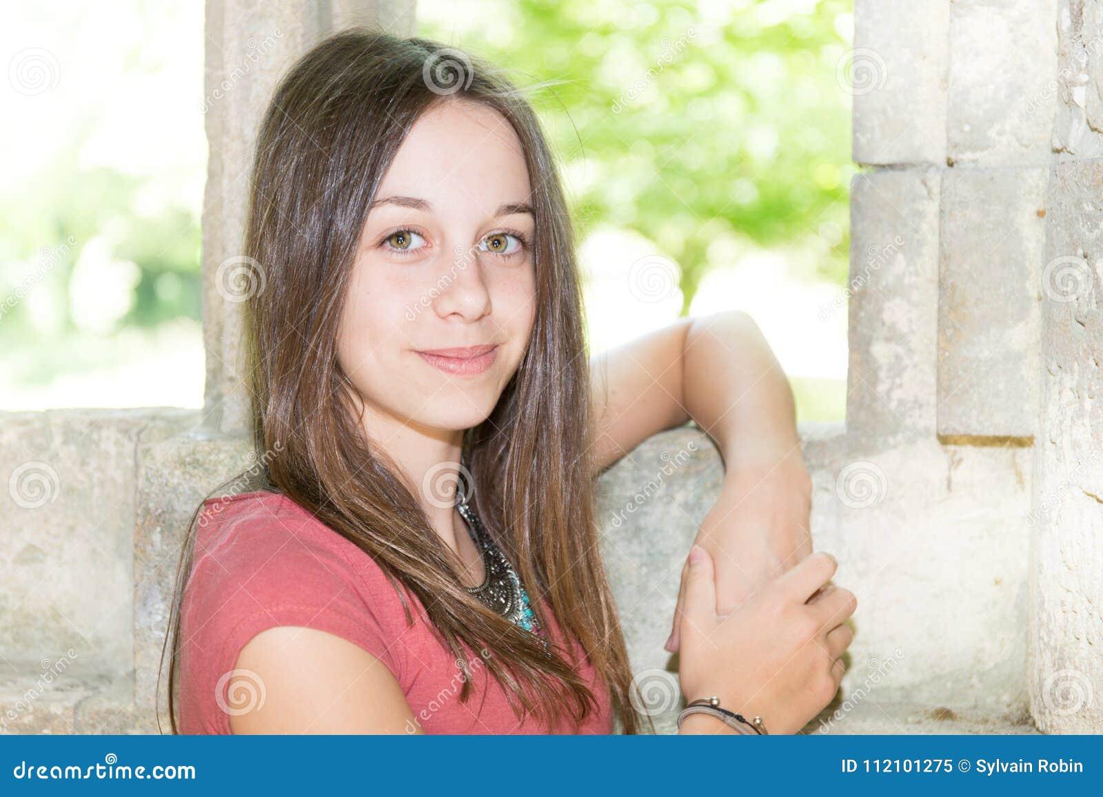 Menina feliz exterior com a parede antiga no verão