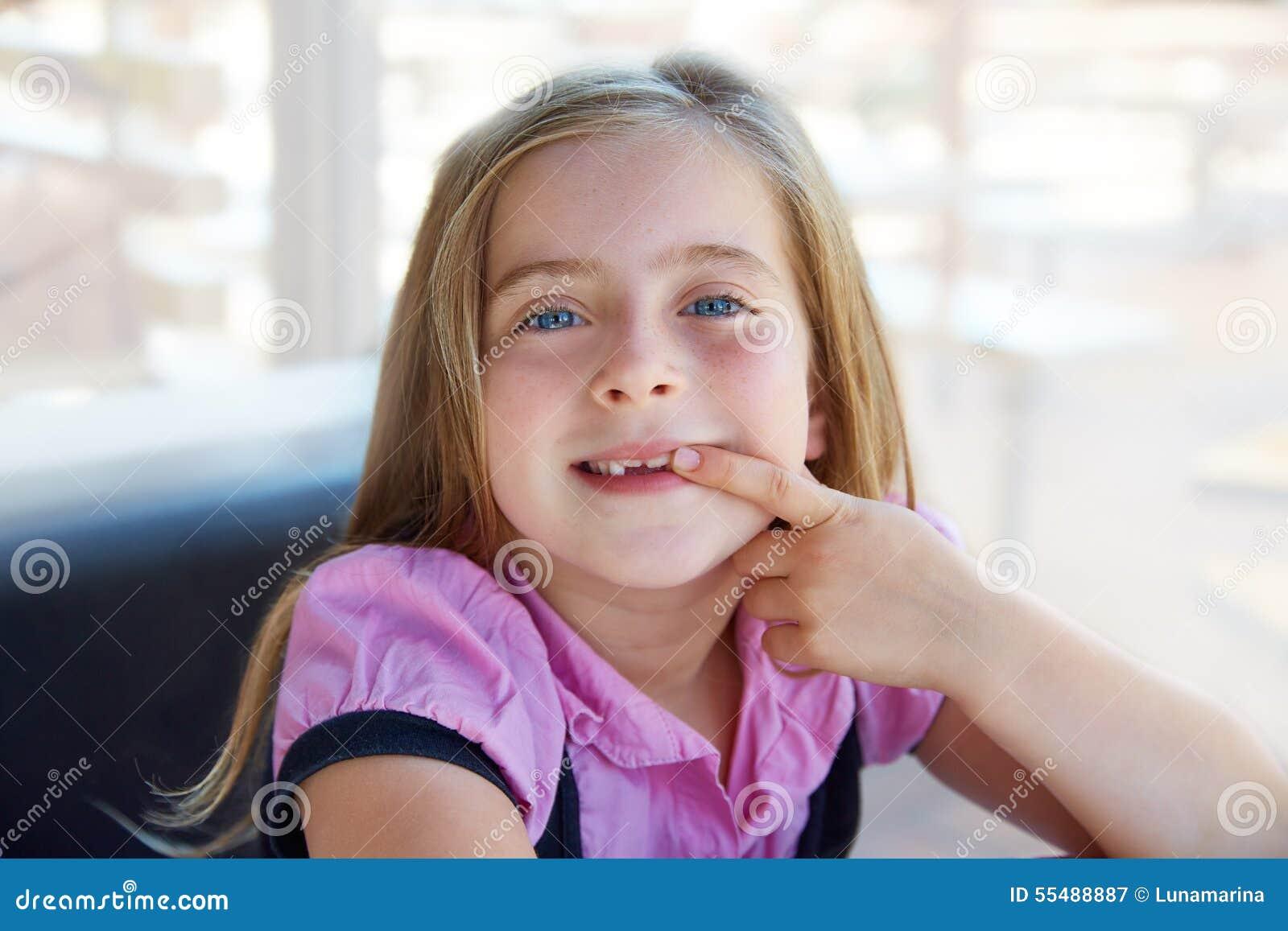 A menina feliz loura da criança que mostra a recortou os dentes