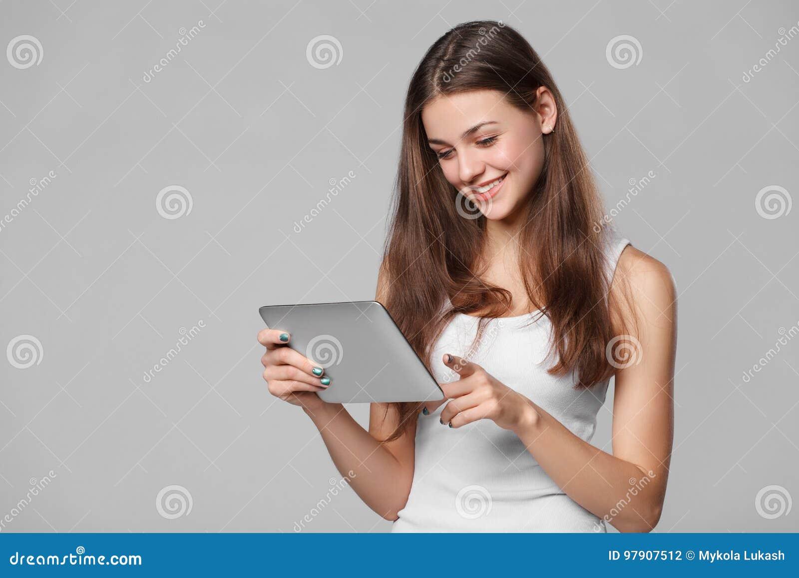 Menina feliz na camisa branca usando a tabuleta Mulher de sorriso com o PC da tabuleta, isolado no fundo cinzento