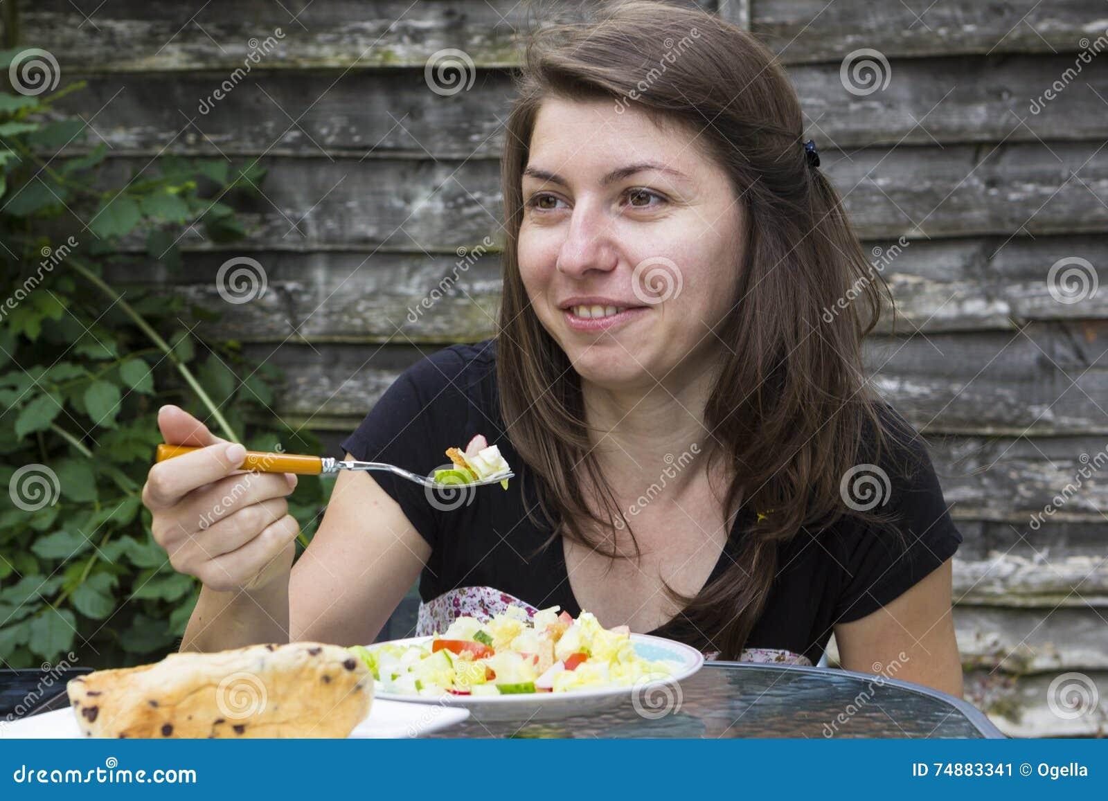 Menina feliz que come vegetais fora