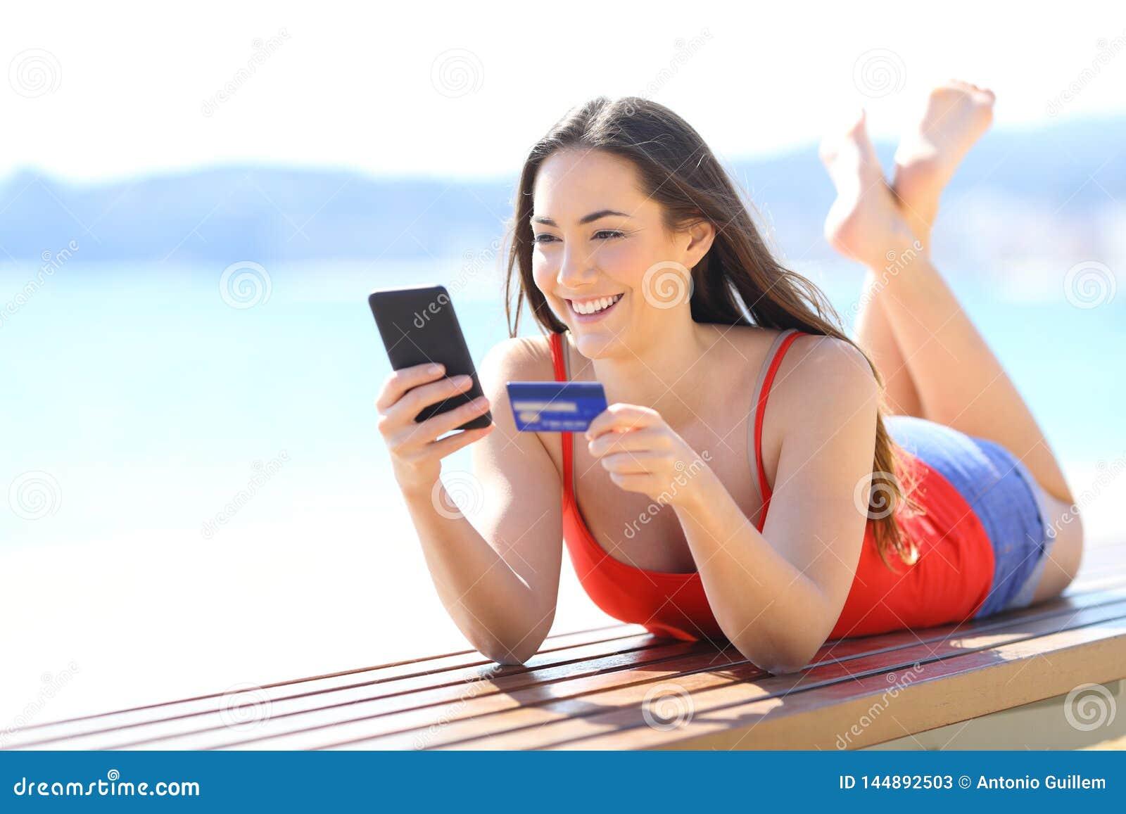 Menina feliz que compra em linha com telefone e cartão de crédito