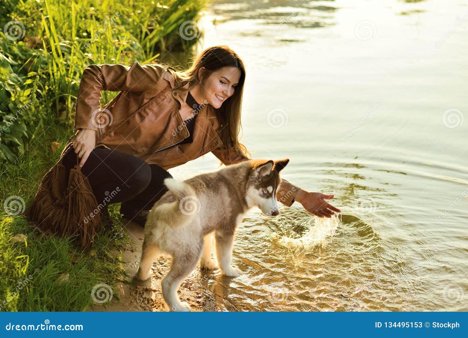 Menina feliz que joga com um cão de cachorrinho ronco no riverbank no outono