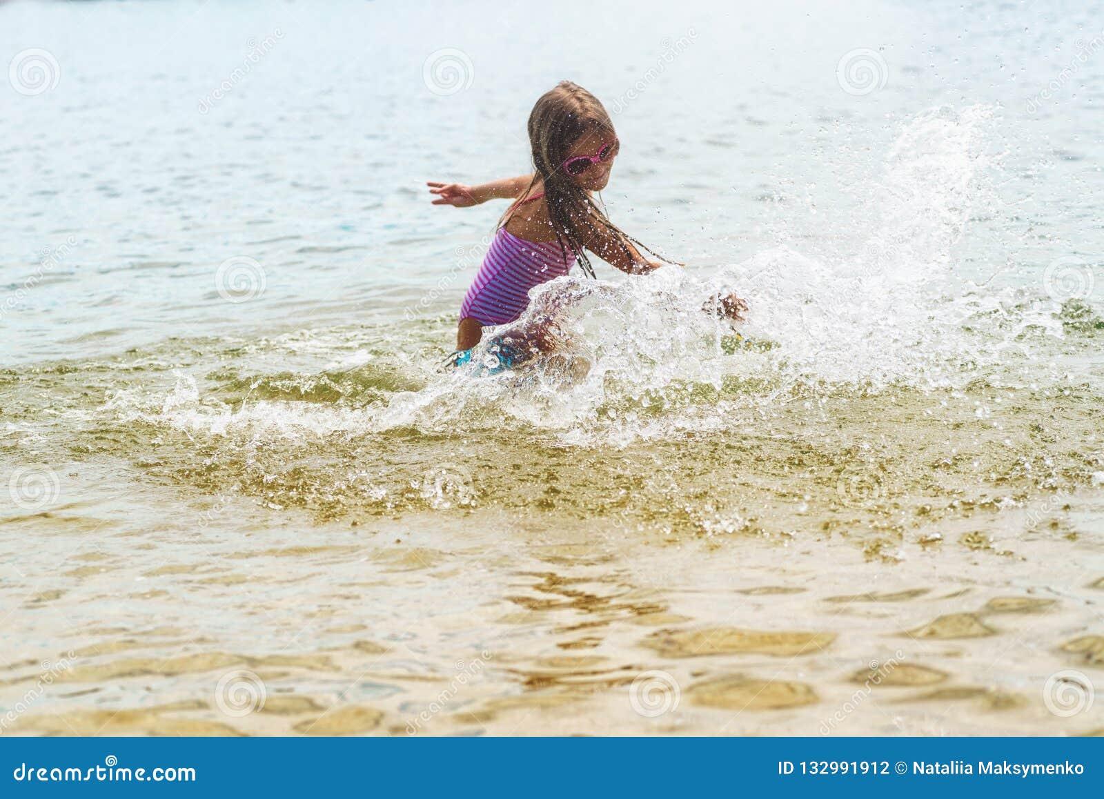 Menina feliz que joga em ondas de água pouco profunda Menina feliz