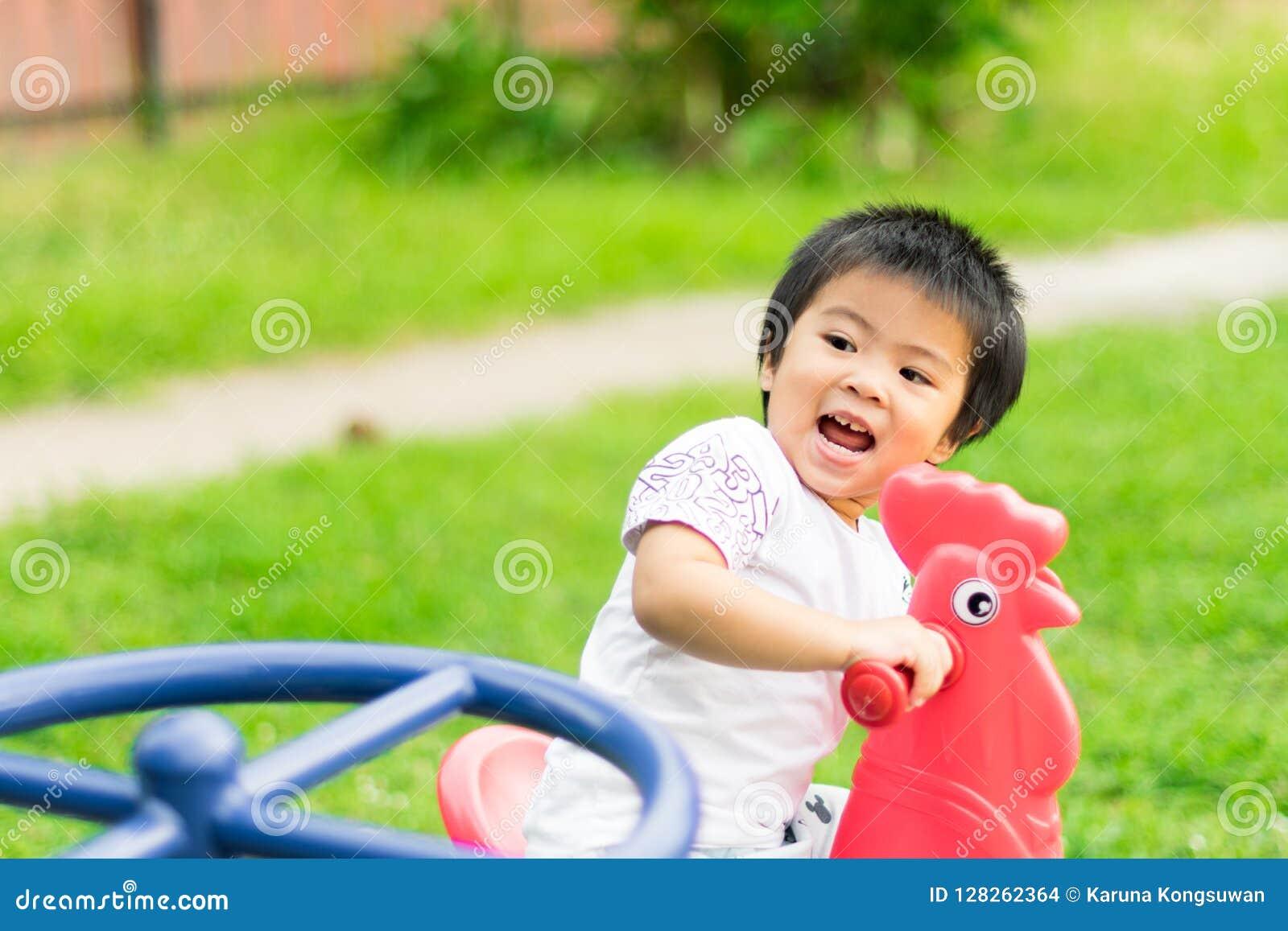 Menina feliz que monta a galinha vermelha no campo de jogos