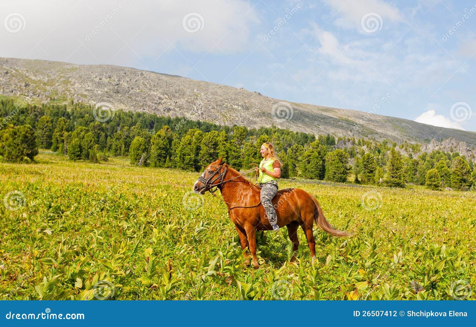 Menina feliz que monta um cavalo