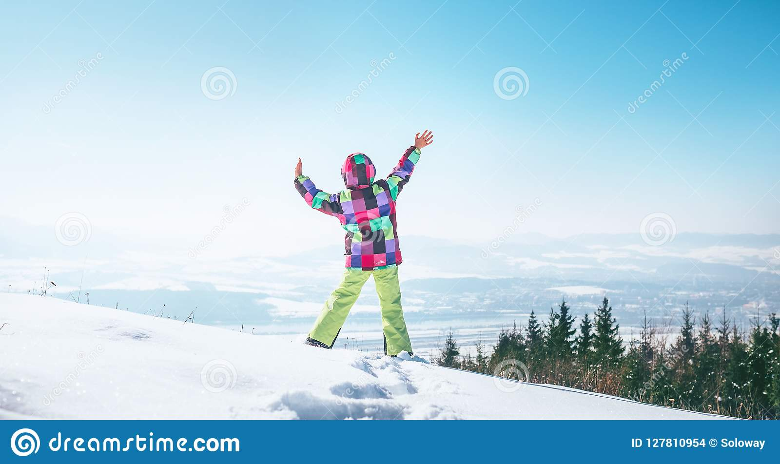 Menina feliz que salta no monte da neve