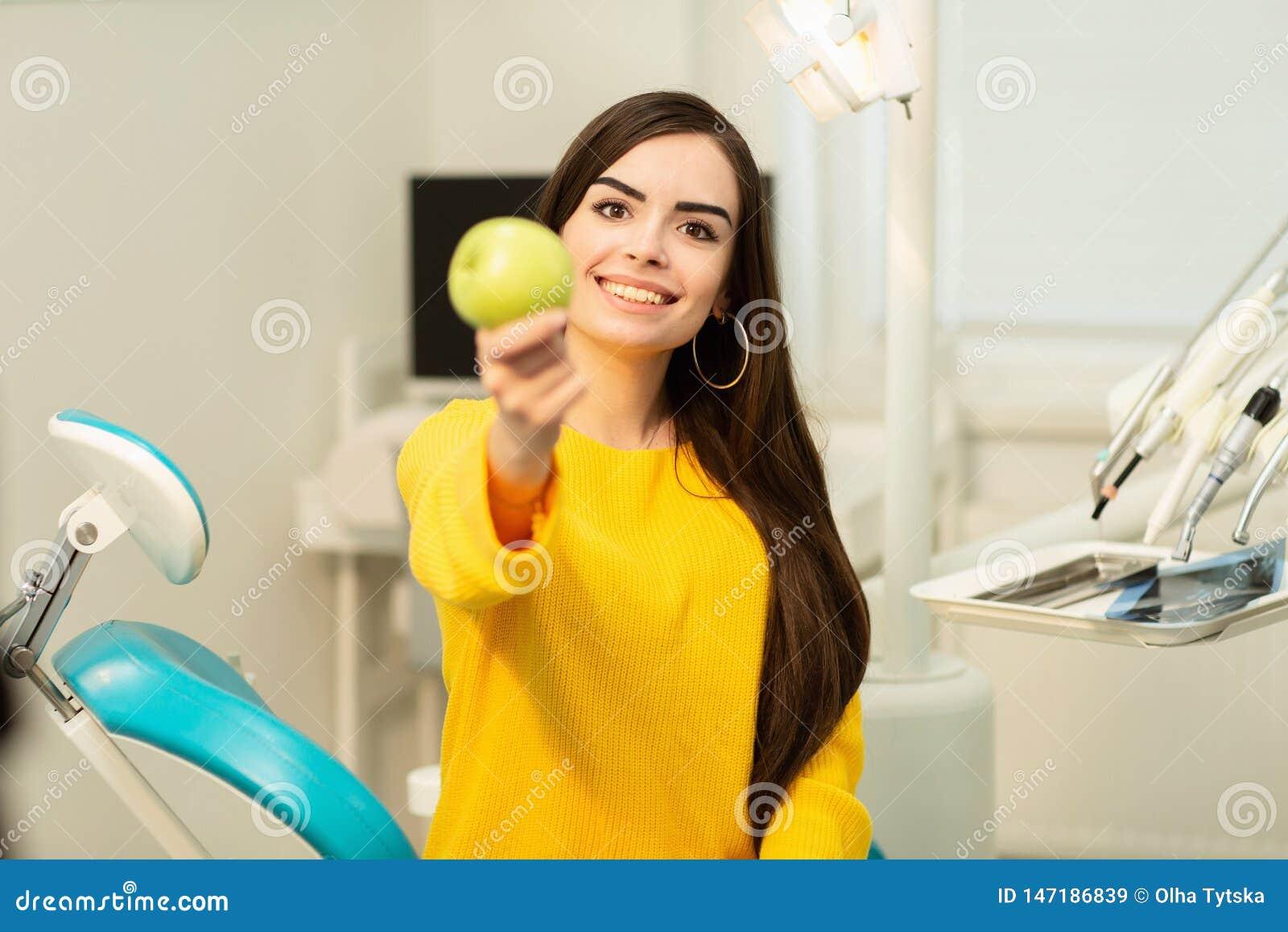 Menina feliz que senta-se na cadeira dental e que mostra ma??s frescas ap?s o tratamento dental bem sucedido