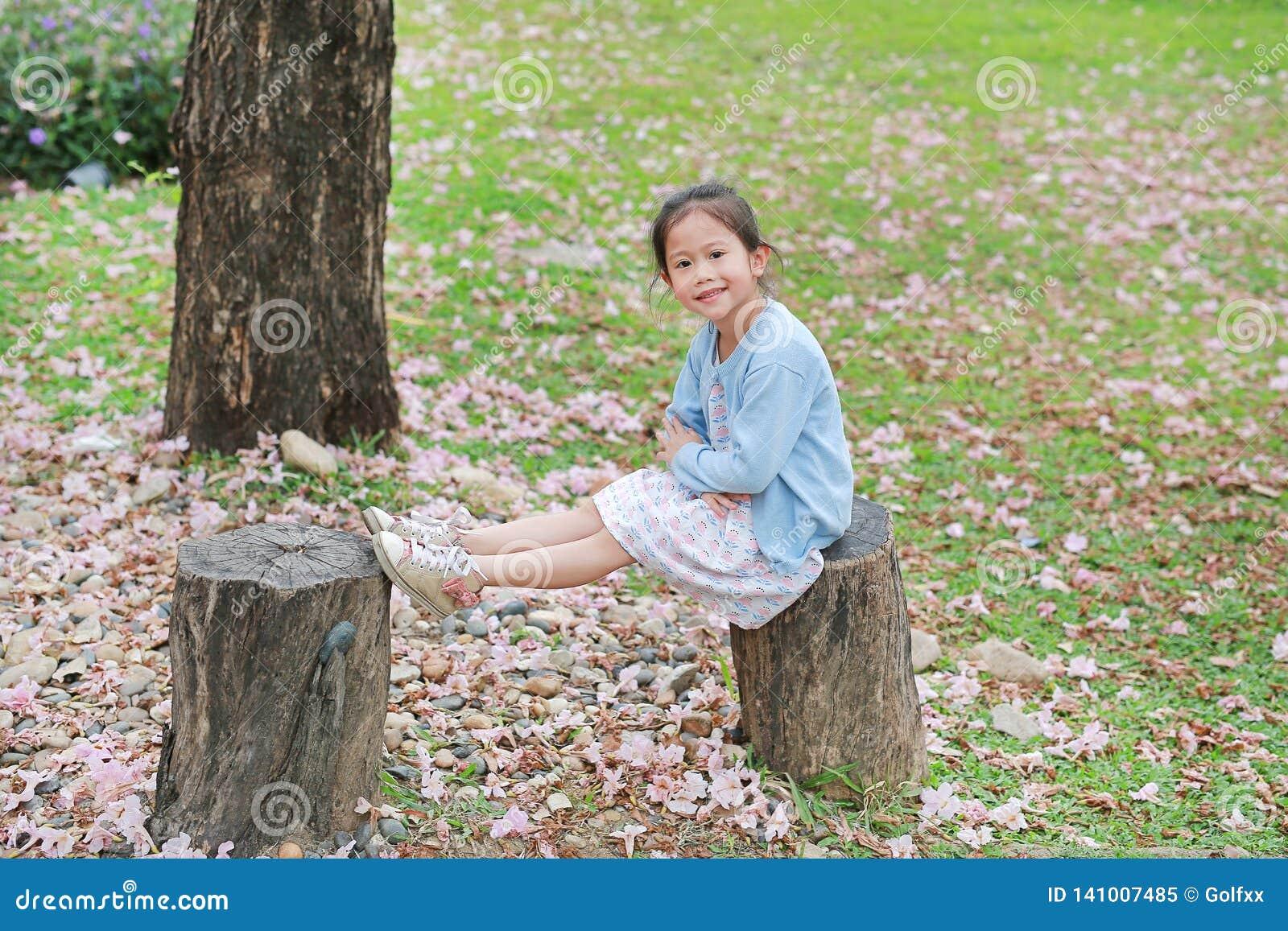 Menina feliz que senta-se nos logs de madeira contra a flor cor-de-rosa de queda no jardim do verão