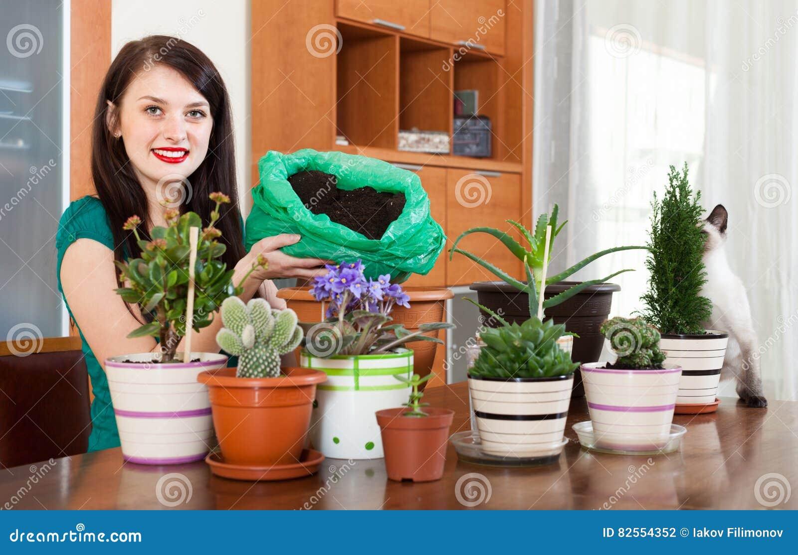 Menina feliz que transplanta flores em pasta
