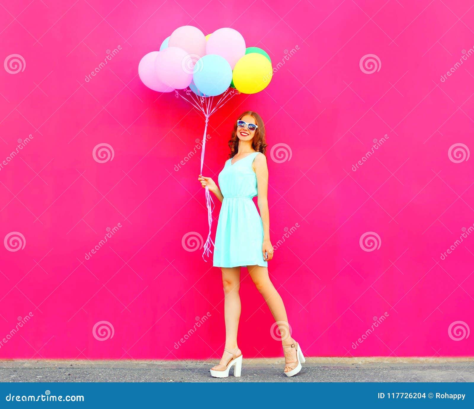 Menina fresca com os balões coloridos de um ar que anda sobre um rosa