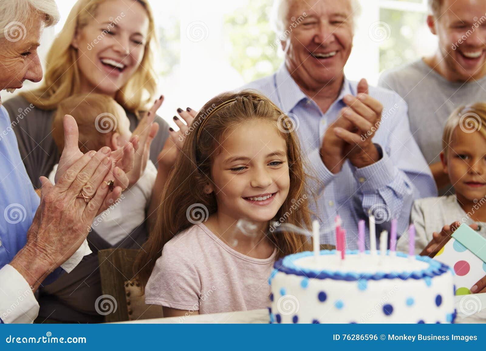 A menina funde para fora velas do bolo de aniversário no partido da família