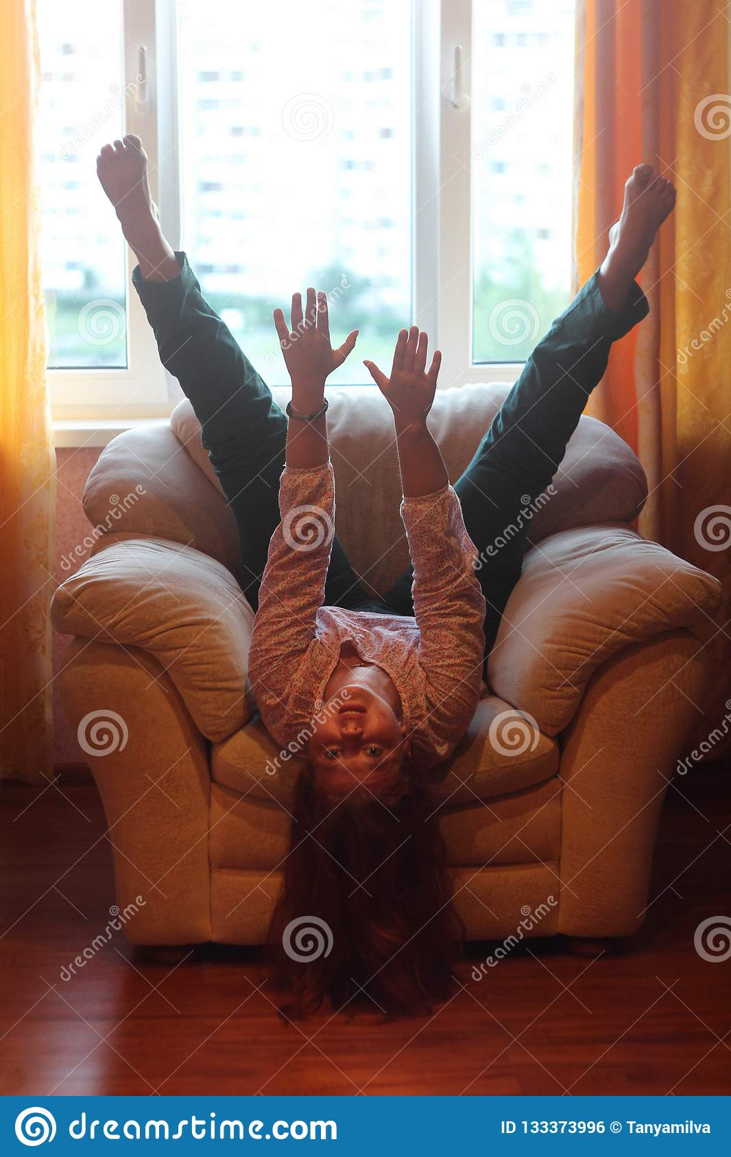 Menina gorda alegre que engana ao redor no sofá