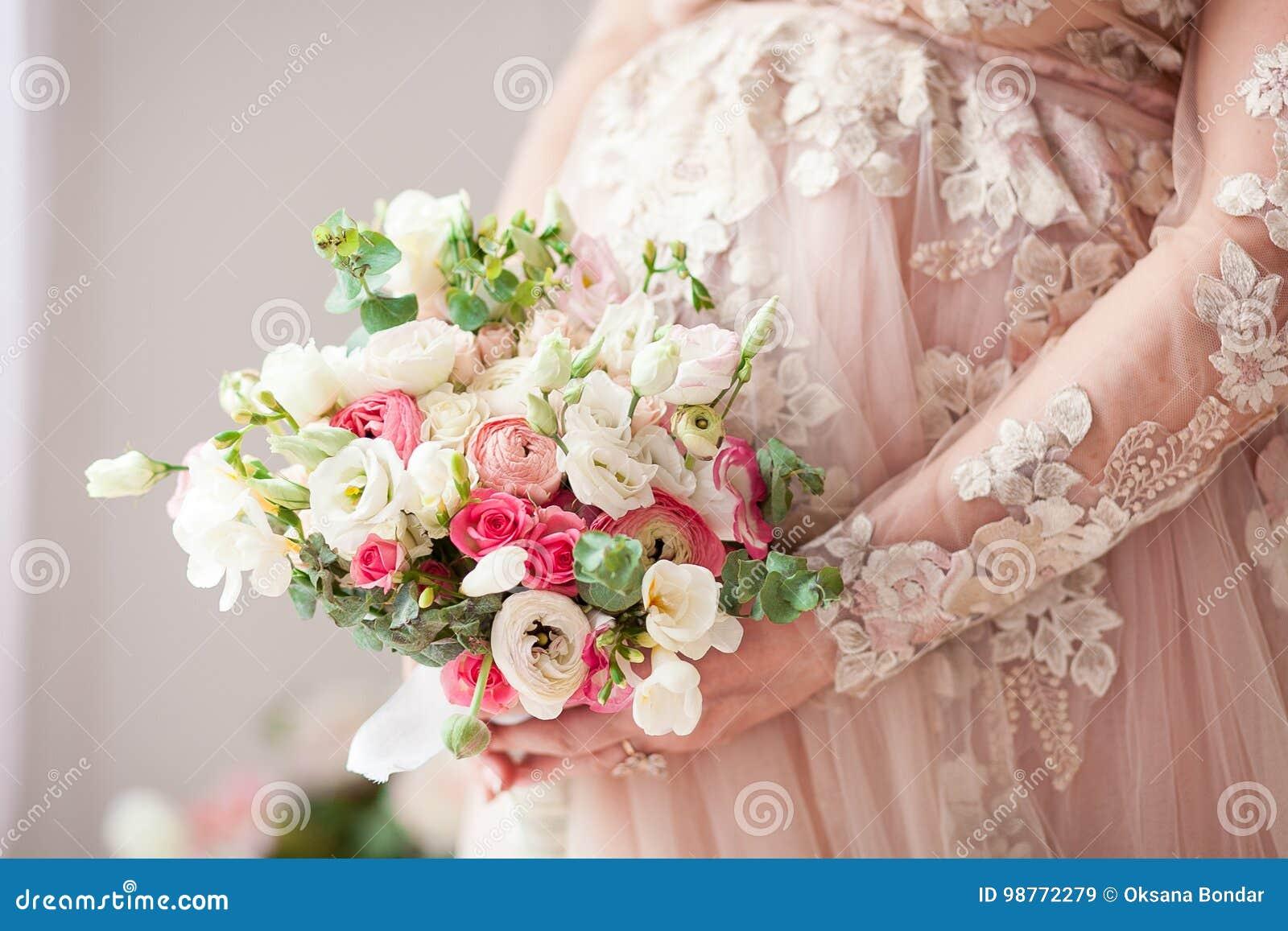 Menina grávida em um vestido bege com um ramalhete nas mãos naughty Esperando um milagre