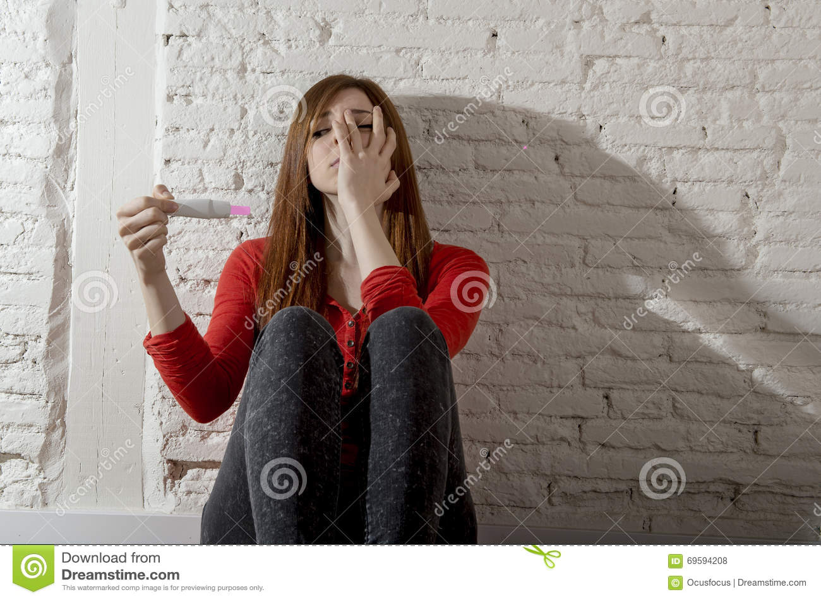Menina grávida preocupada assustado do adolescente ou mulher desesperada nova que guardam o teste de gravidez positivo